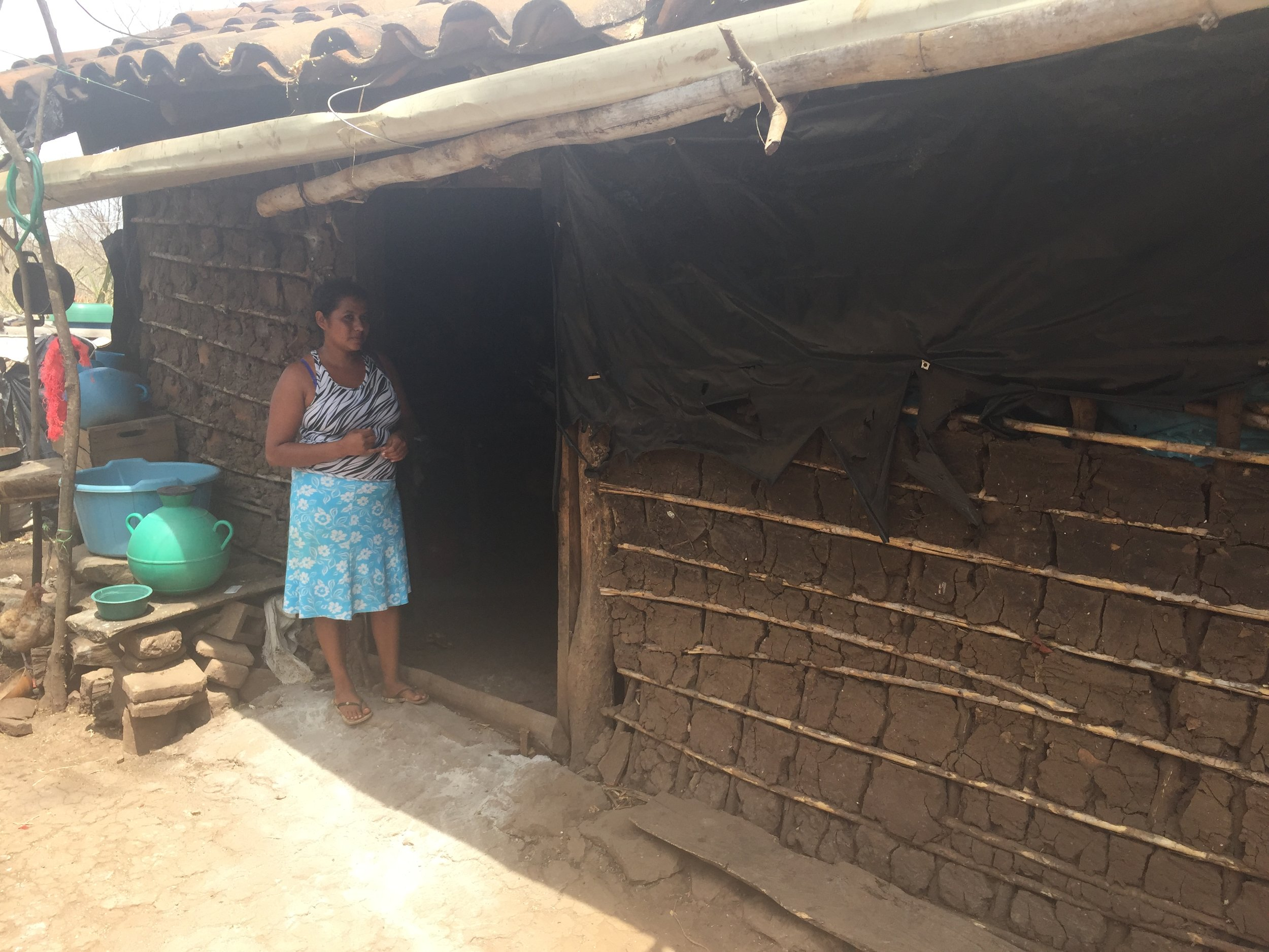 A woman waits for her children outside her home, now improved by the plastic to keep the rain out. Her water and washing containers are just behind her, ready for their next trip to the river.