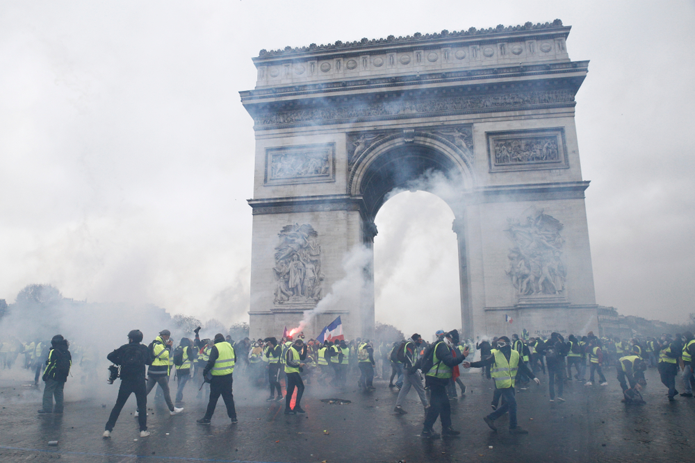 """Paris rioters in """"yellow jackets"""" amid tear gas at the Arc de Triomphe. Credit: Shutterstock.com"""
