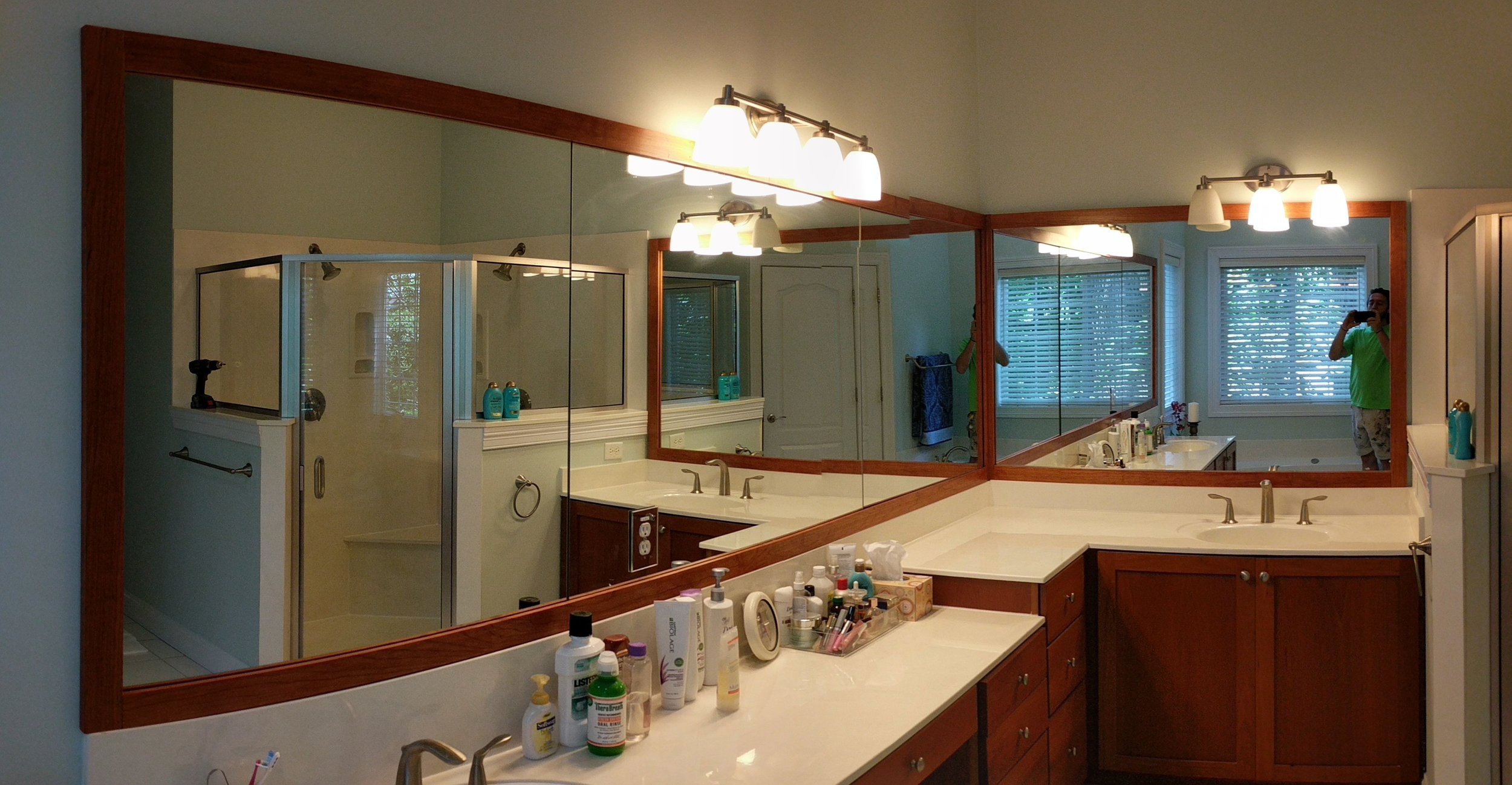 We fabricated and installed this cherry wood trim on the mirrors to match the existing cabinetry.