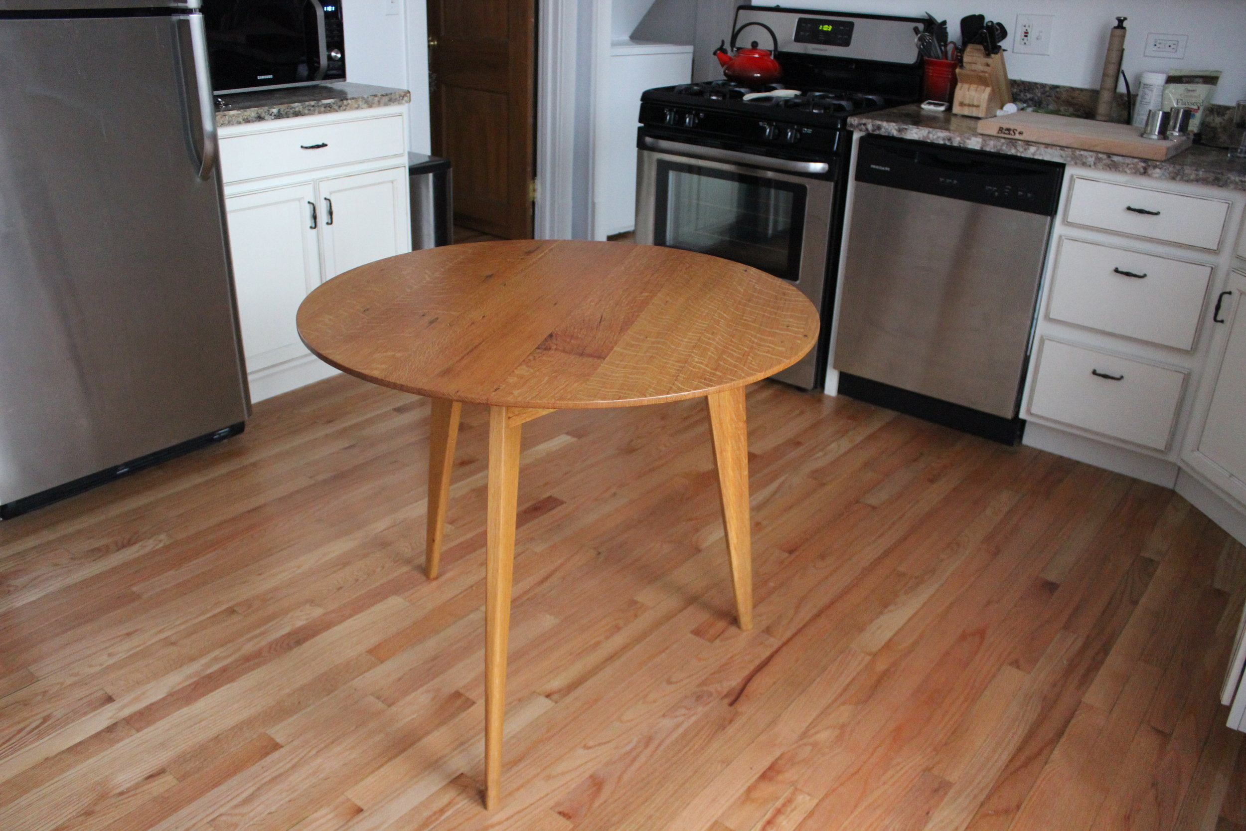 Custom designed 3 legged round kitchen table made from reclaimed white oak.