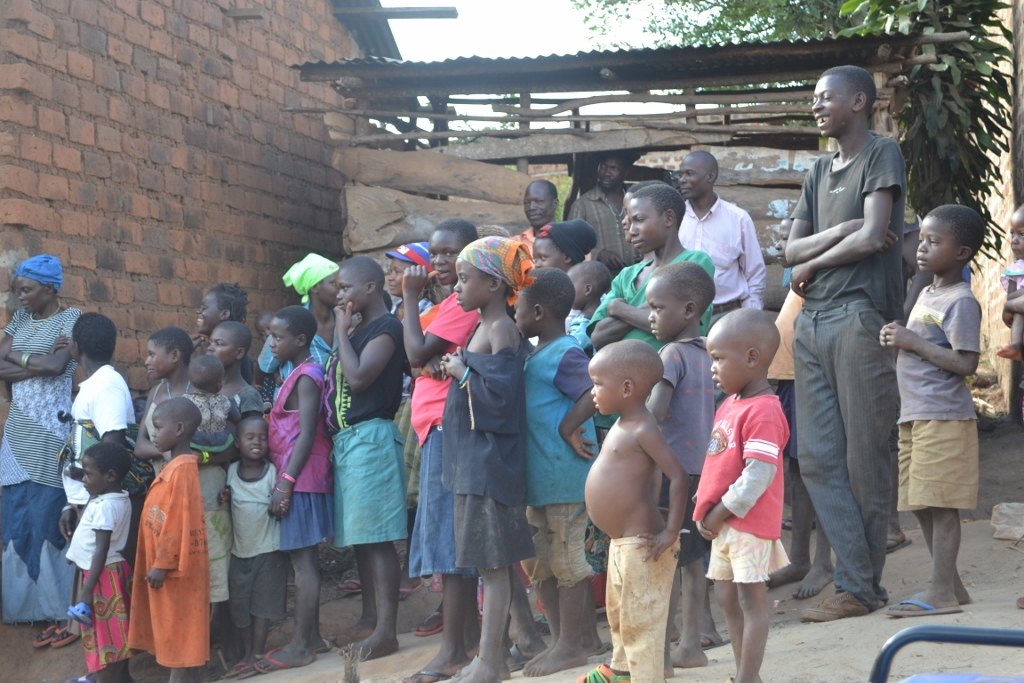 Katuuso village children and community members watch on as Raising Voices run their outreach program.