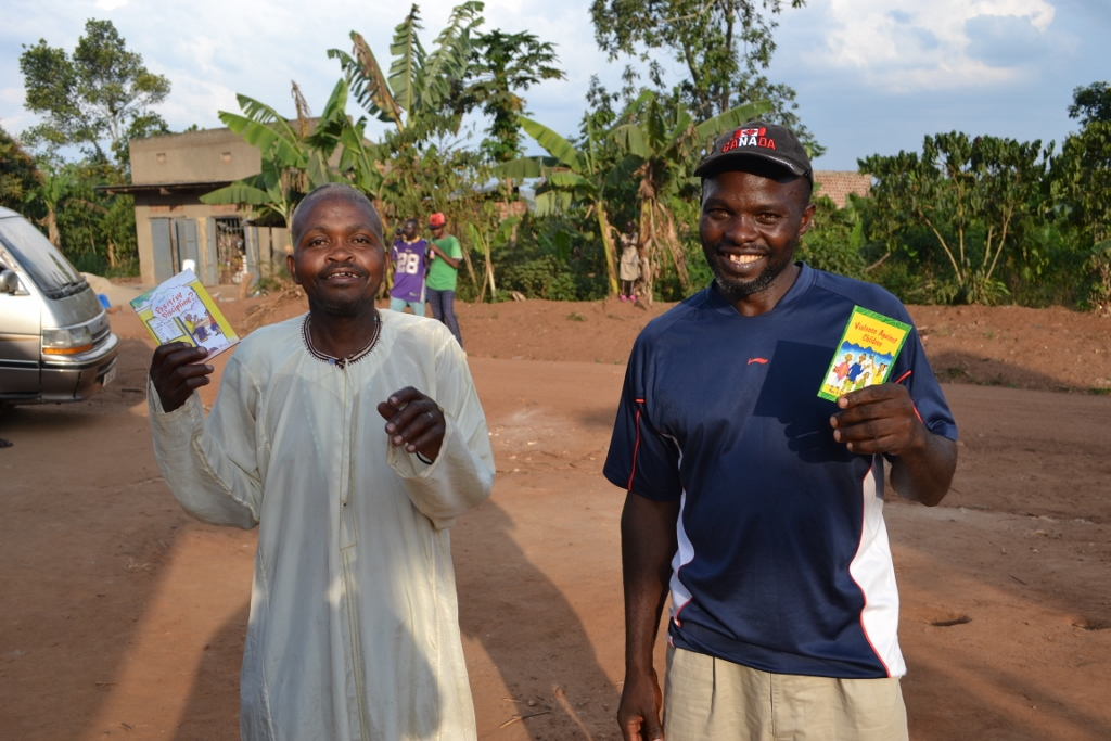 Two Katuuso community members take home pamphlets with information on child abuse and women's rights after the outreach program.