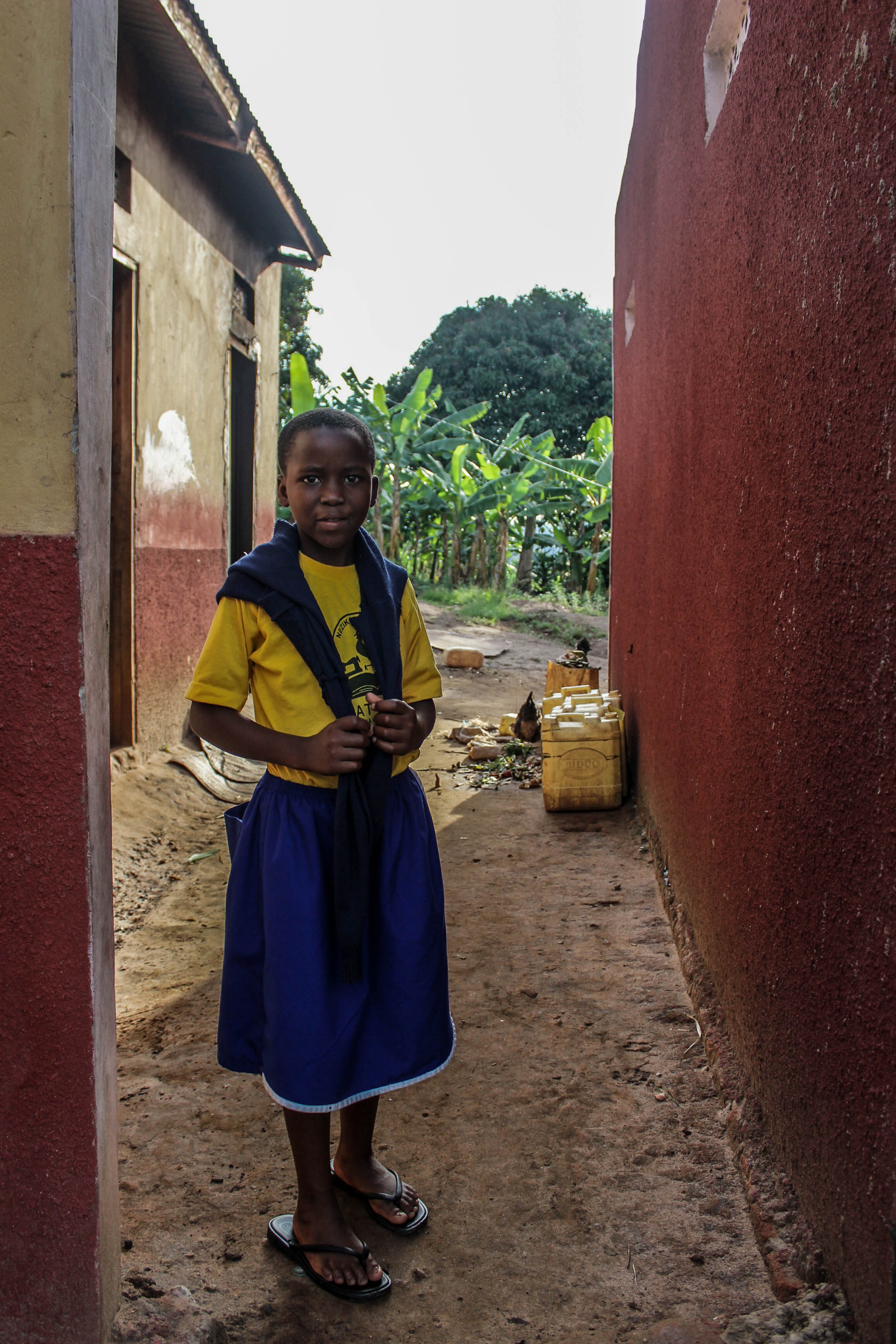 Goretti's home is a simple structure surrounded by her uncle's crops. The yellow containers behind are a constant sight in rural Uganda as they're used to carry water from a well. This can be a long journey for many children to carry many litres of water on their backs each day.