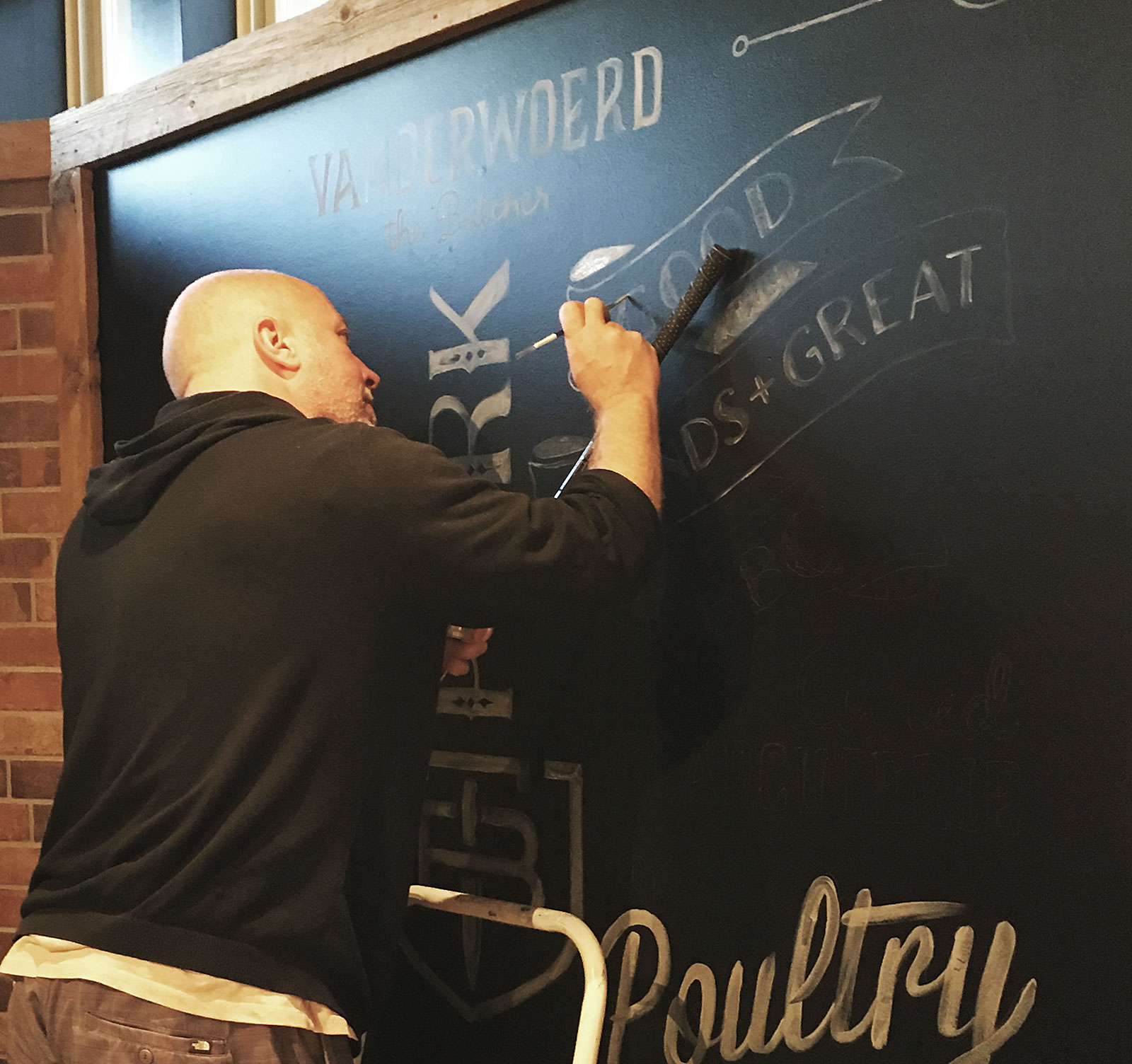 John painting the chalkboard mural at The Butcher