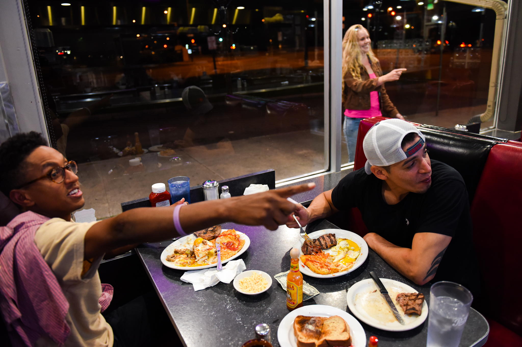 4 a.m.: Adam Tewahade (left) points as a woman smoking a cigarette tries to get her friend's attention inside the Denver Diner. Tewahade and Joe, across from him, met earlier in the night on Larimer Street.