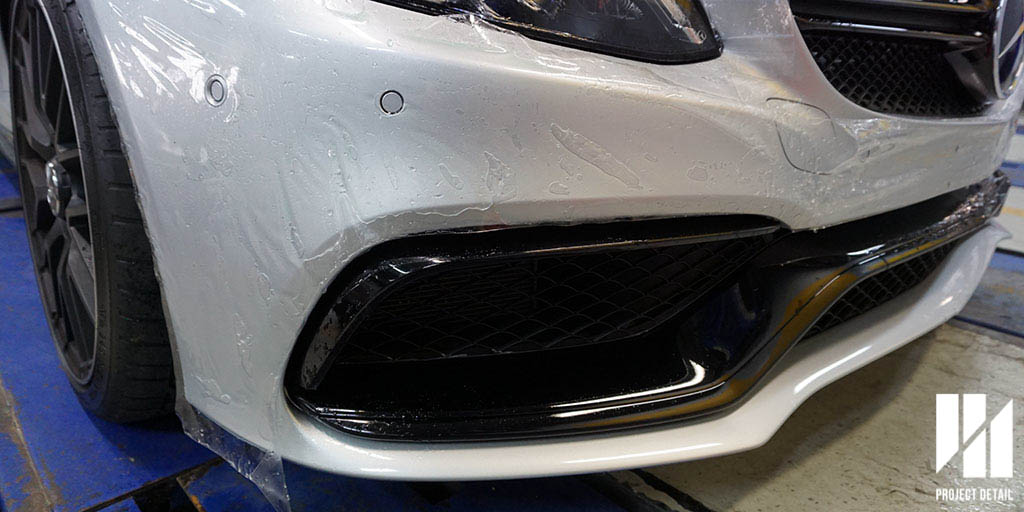 2016 Mercedes Benz C63S AMG Sedan undergoing XPEL PPF installation. This is a  PRE-CUT Template  professionally designed for the the complex front bumper. Notice the parking and driving sensors on the corner.