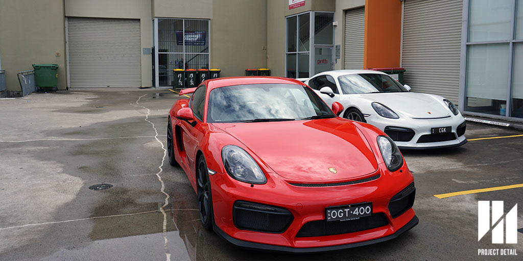 Two Porsche Cayman GT4's Carrera White and Guards Red both PPF protected by Project Detail.