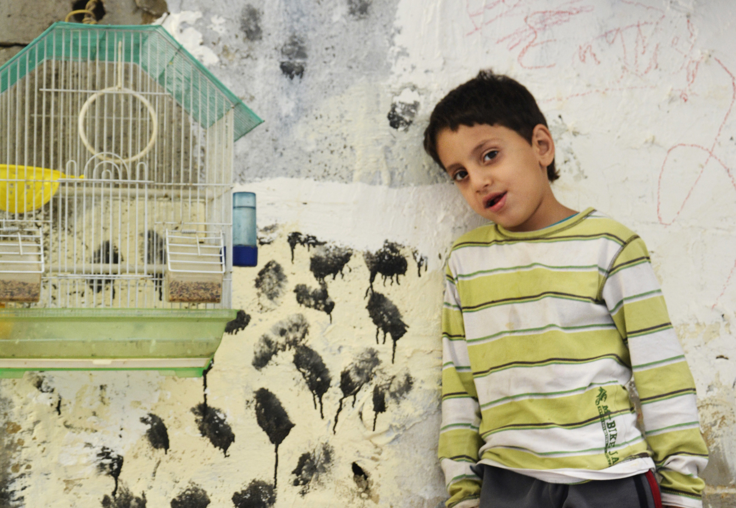 """Hassan Basyouni, 12, Palestinian-Syrian, stands by his pet bird. """"Back in Syria, we had a lot of birds,"""" his father said, smiling weakly, """"I try to get some to keep him happy."""""""