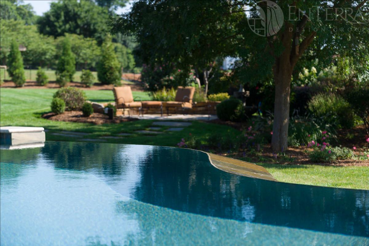 Vanishing edge pool overlooking the rustic patio seating area.