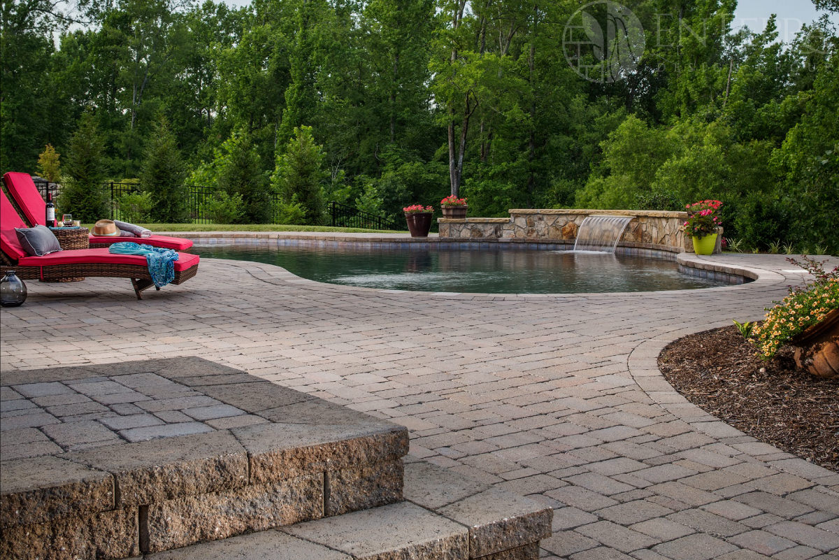 This freeform pool with a raised beam water feature creates a welcoming outdoor living environment for this family to enjoy.