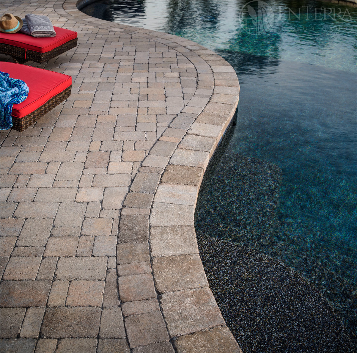 The tumbled paver pool deck & coping nicely compliment the darker Pebble Tec pool finish.