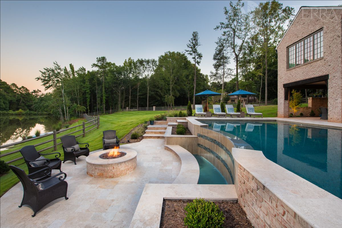 The pool & hardscape are terraced to work with the natural grade sloping down towards the pond.