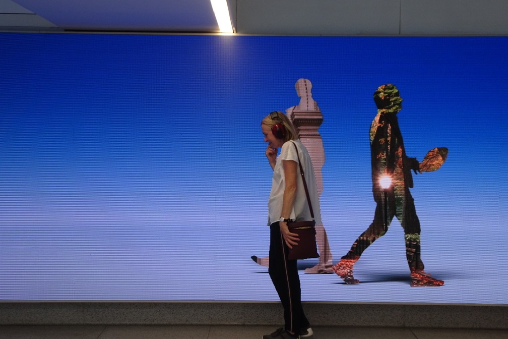 Kubisch pausing to listen in front of a giant LED display in Penn Station's remodeled 8th-Avenue waiting area. photo credit: Christina Kubisch