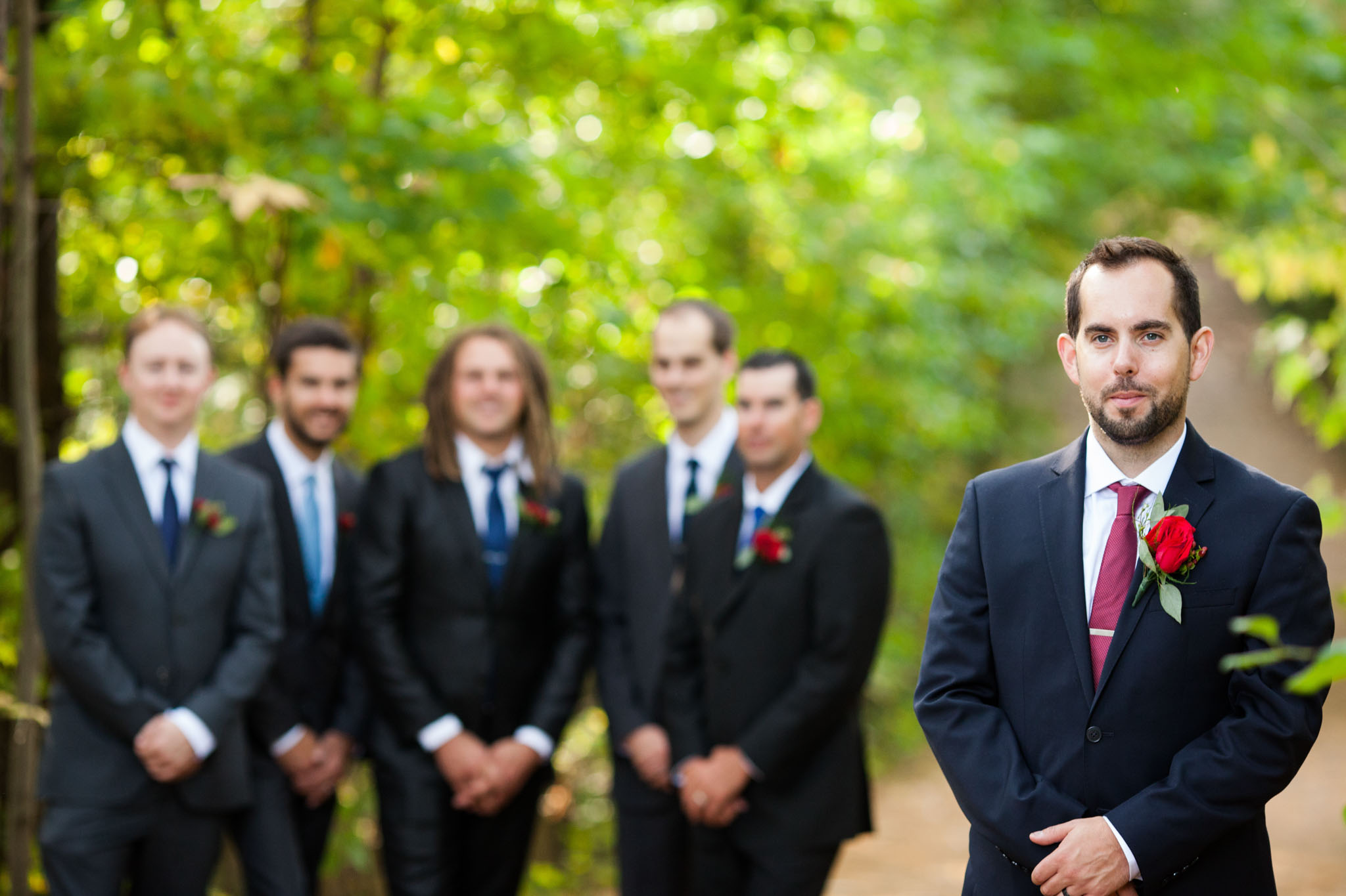 groom with red tie and red boutonniere with groomsmen in back ground in natural wooded area - wedding photography.jpg