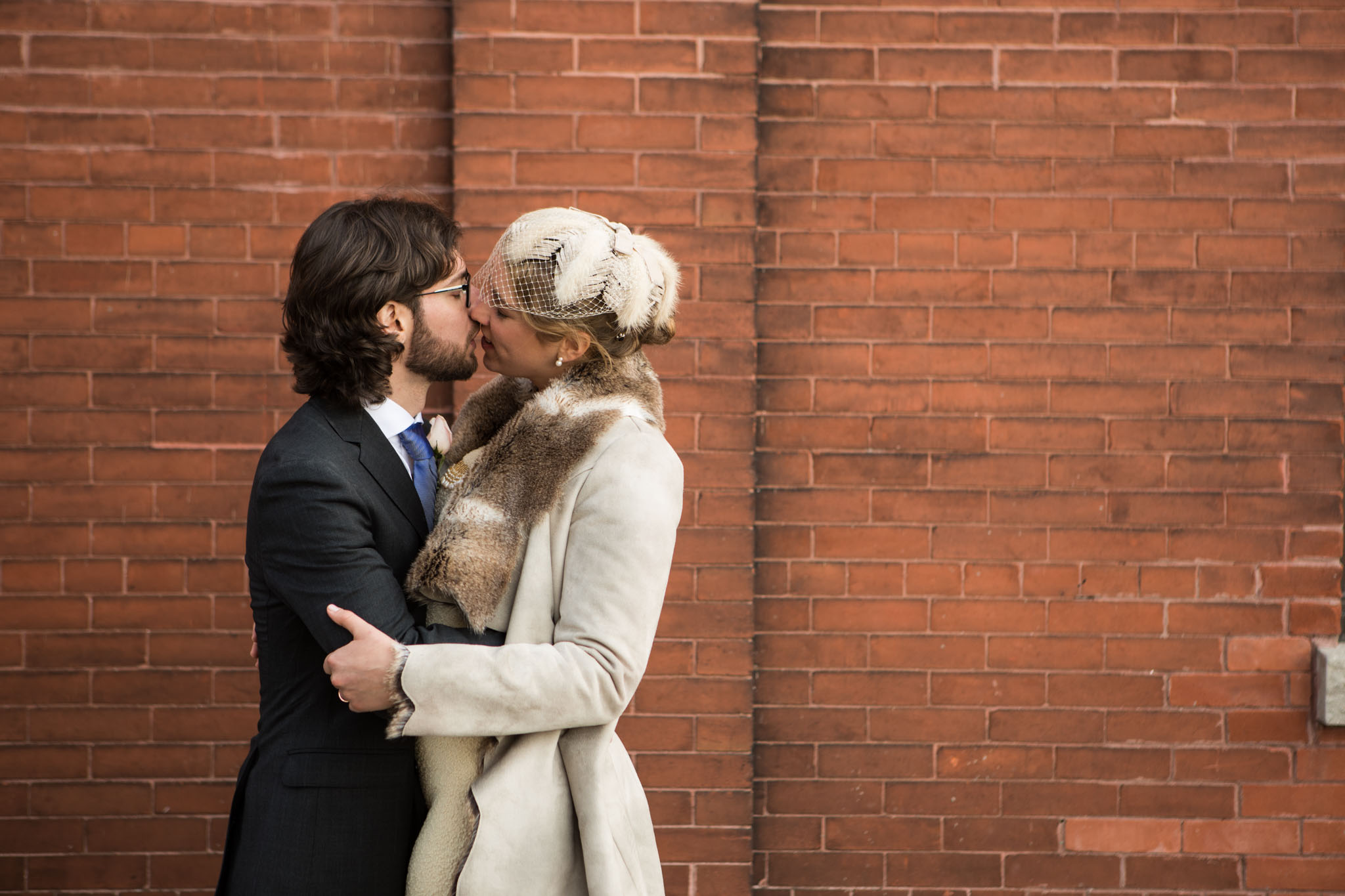 wedding portrait red brick wall background passionate kiss.jpg