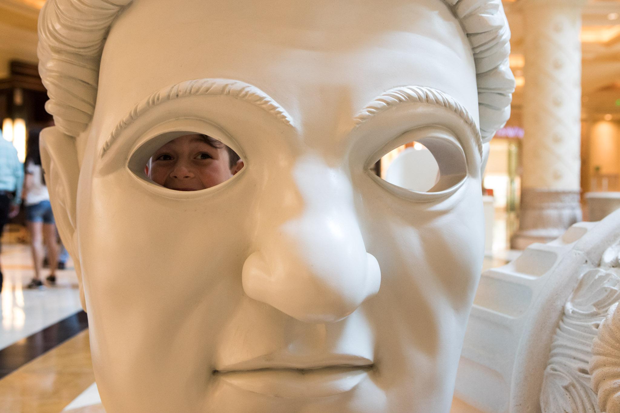 little boy peaking out eye socket of a large face statue.jpg