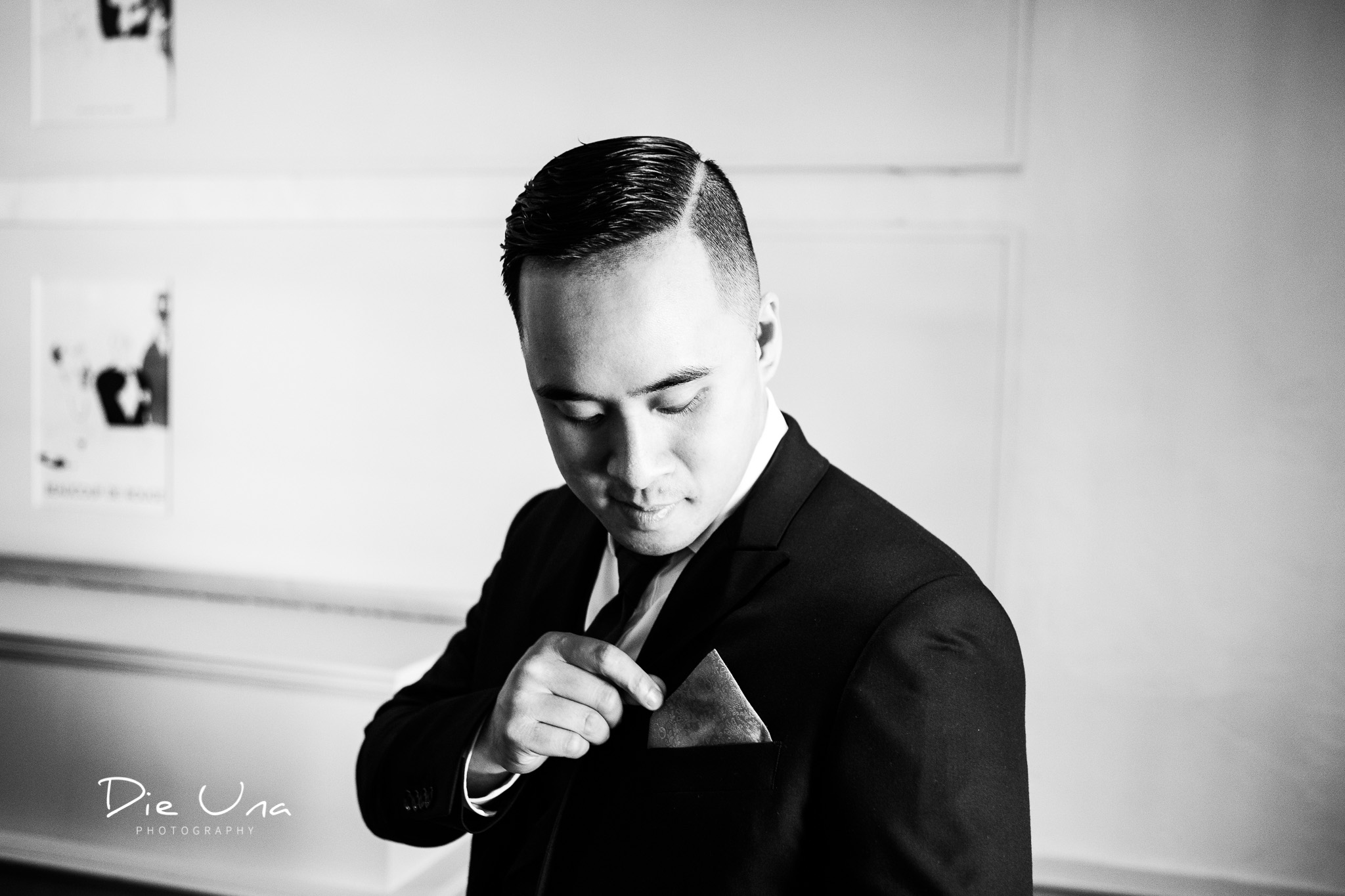 black and white portrait of groom fixing pocket square.jpg