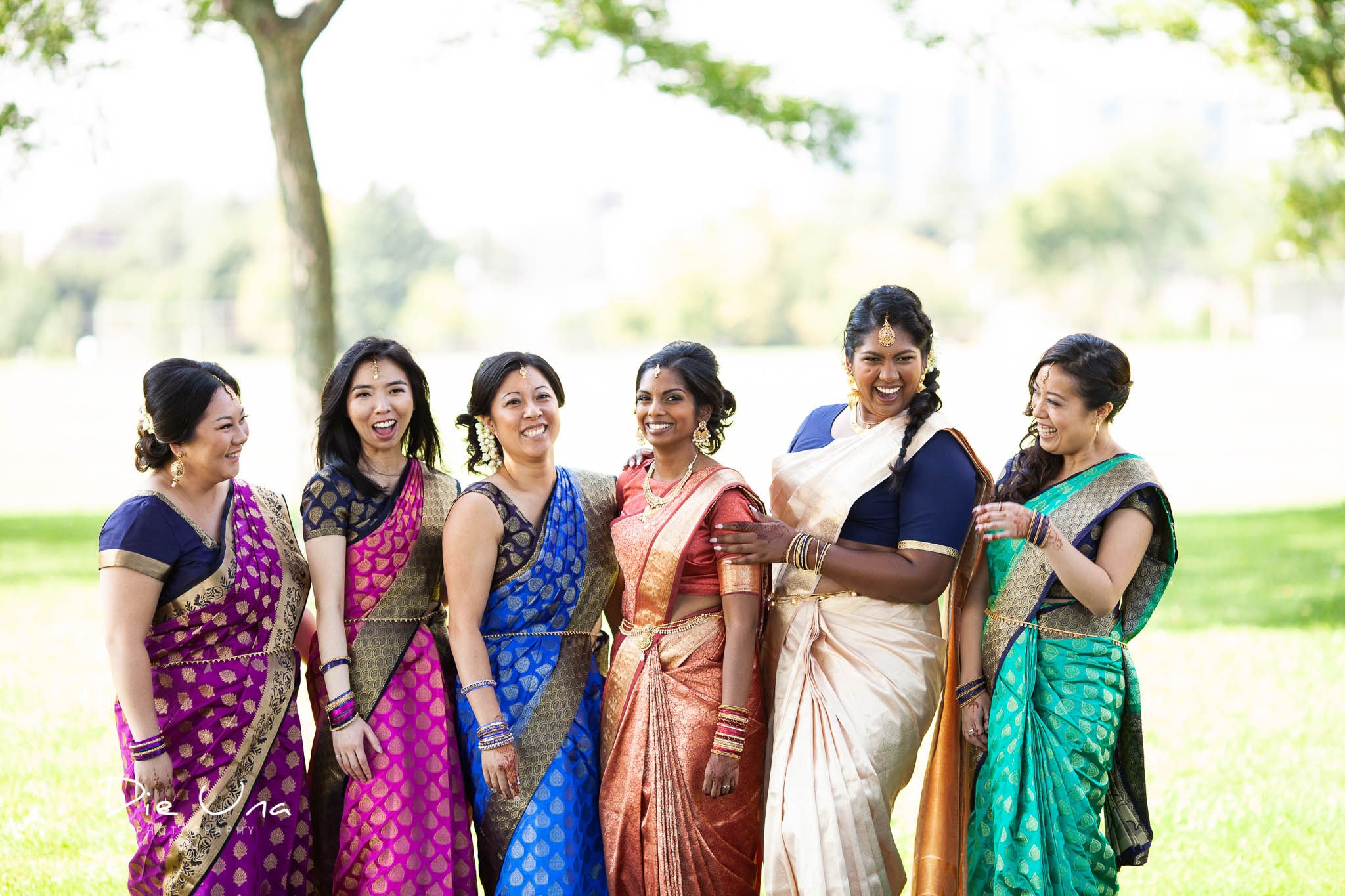 bride and bridesmaids wearing sarees and laughing outside.jpg