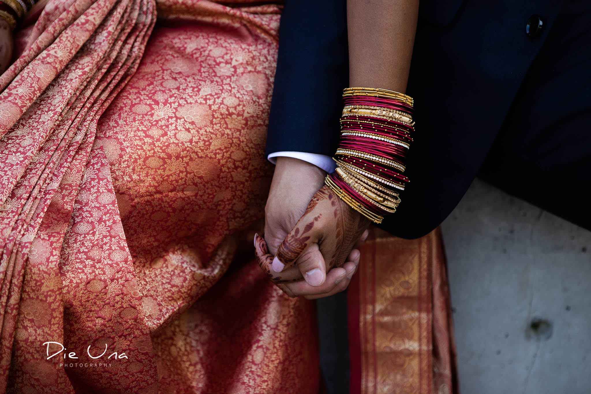 bride and groom holding hands bride wearing red and gold bracelets.jpg