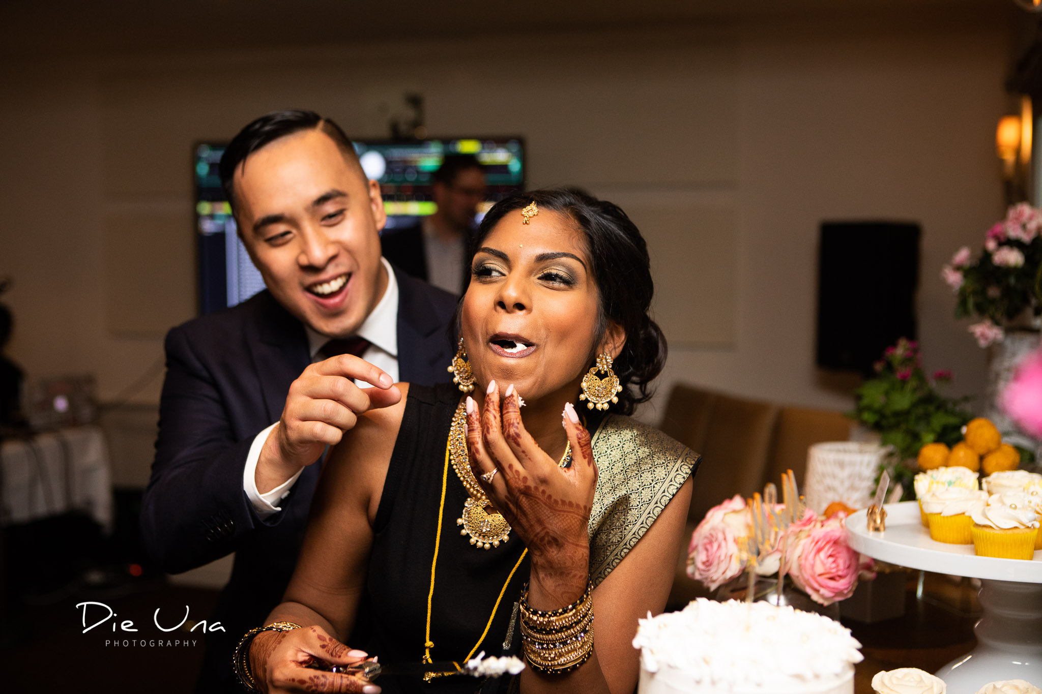 bride eating the cake before groom and laughing.jpg