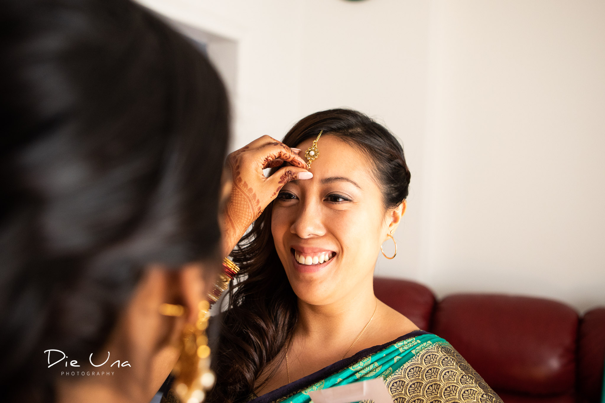 bride putting a bindi on a bridesmaid .jpg