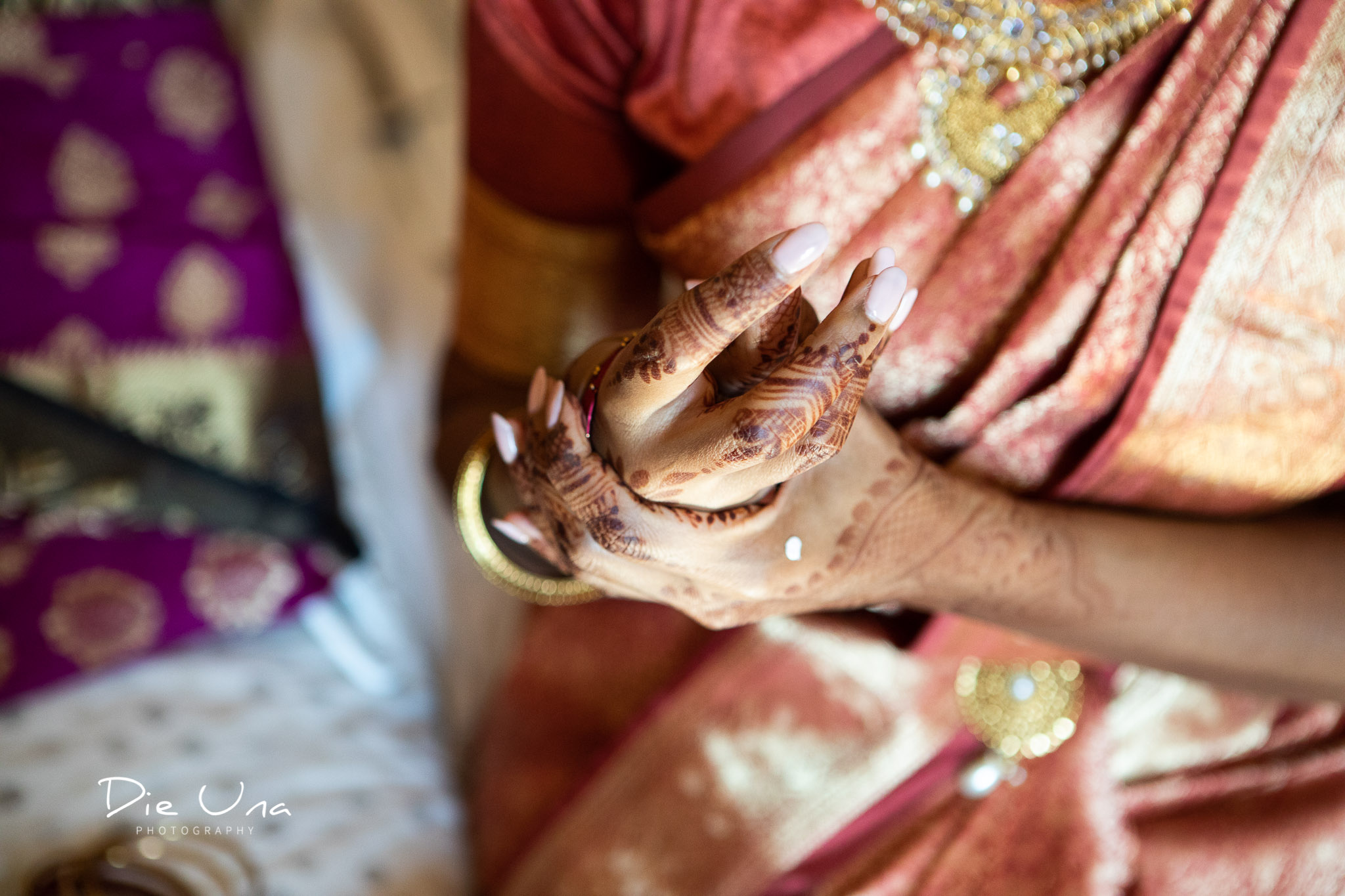 bride putting on wedding bracelets while wearing saree.jpg