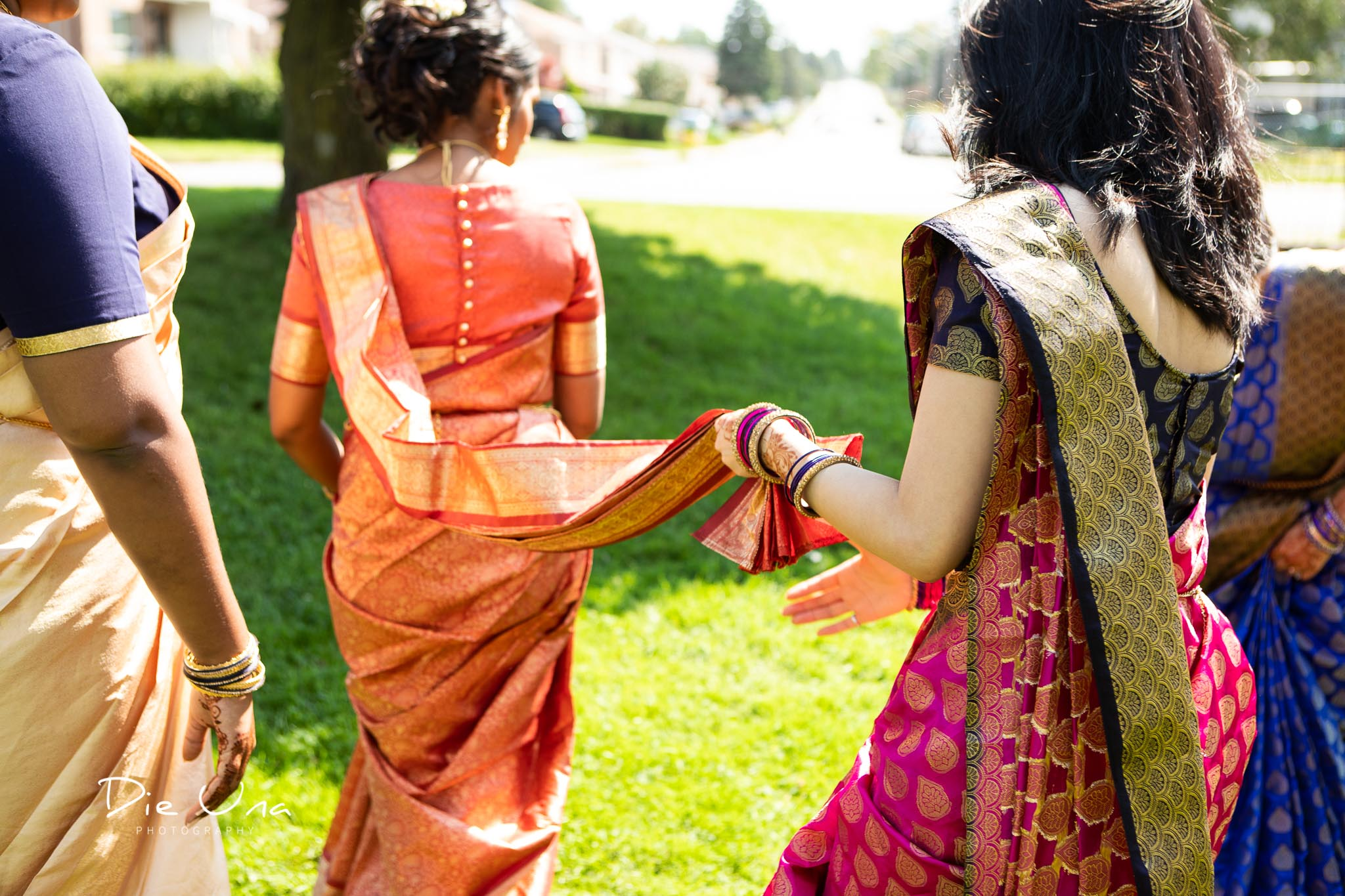 bride walking while bridesmaid holds saree.jpg