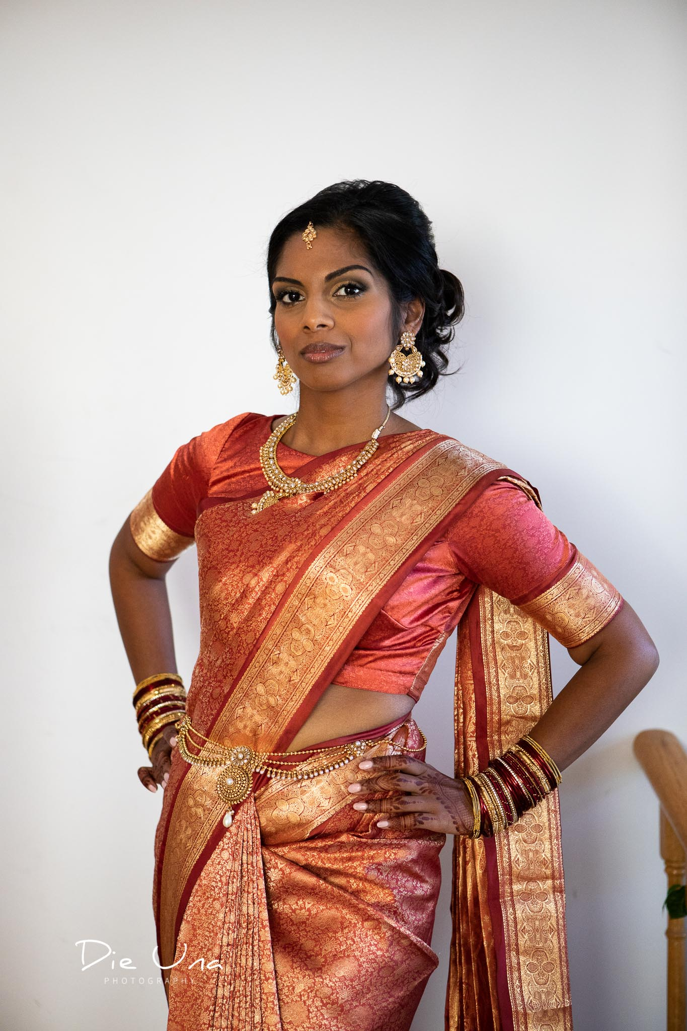 bride wearing red and gold saree.jpg