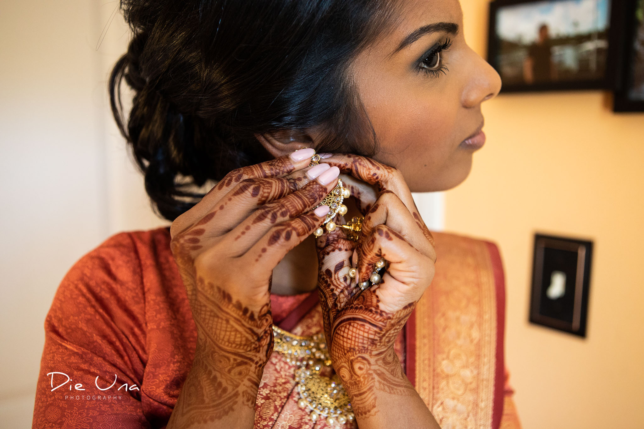bride with henna tattooed hands putting on earrings.jpg