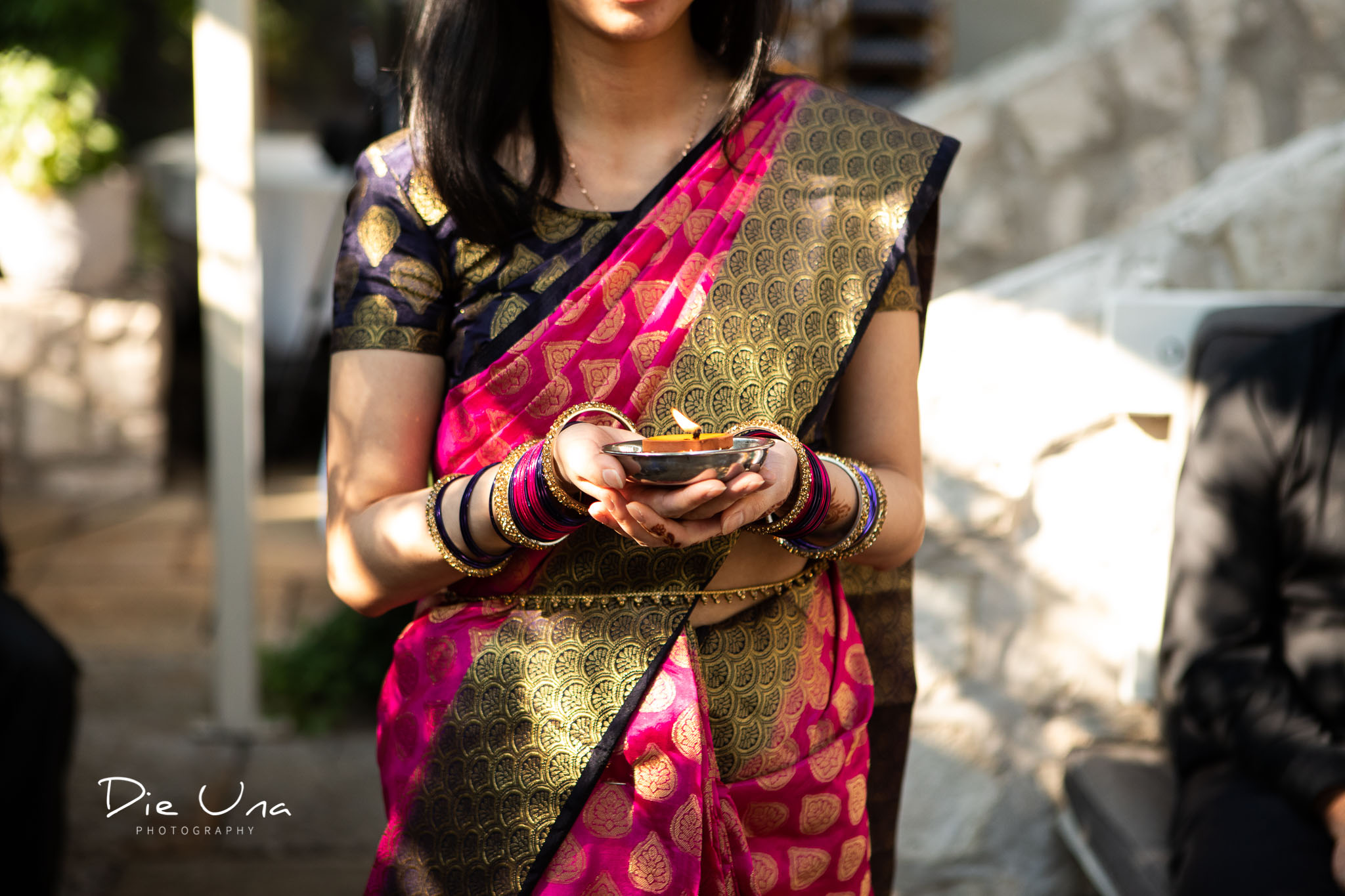 bridesmaid wearing saree carrying candle down the aisle.jpg