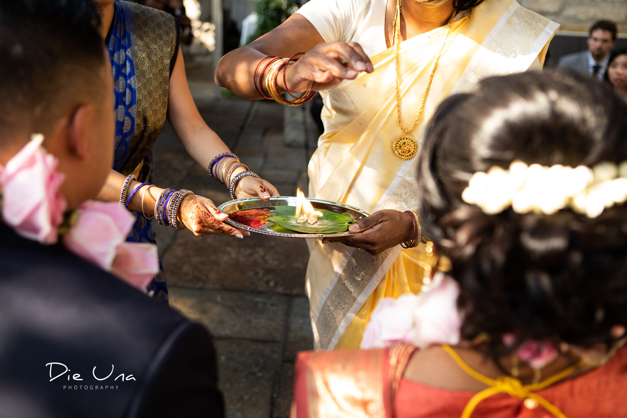 close up of tray with red powder and flame to bless the bride and groom during Hindu wedding.jpg