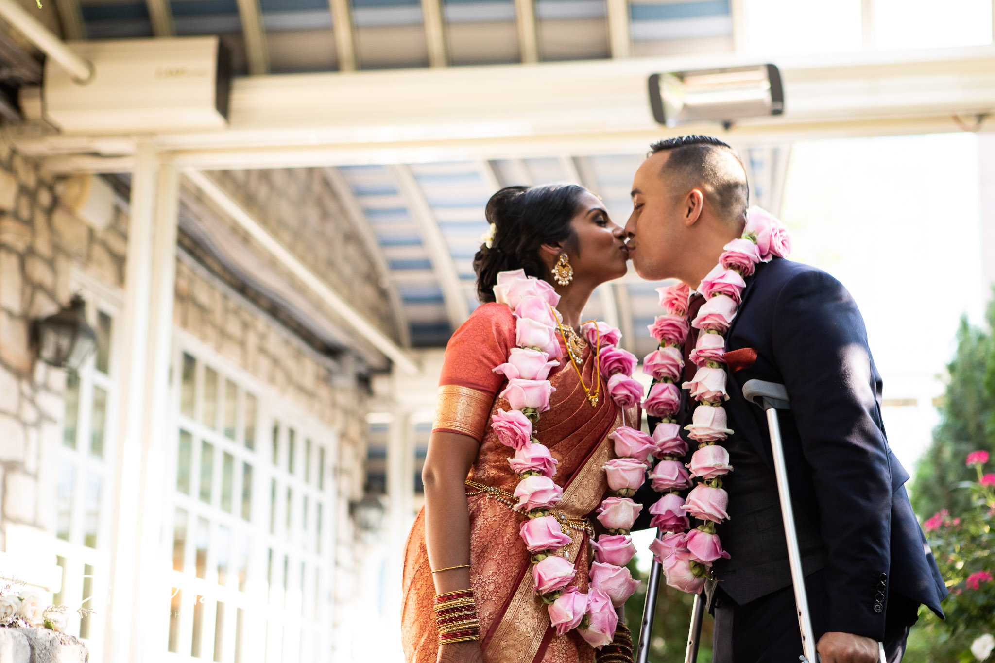 first kiss with groom standing using crutches.jpg