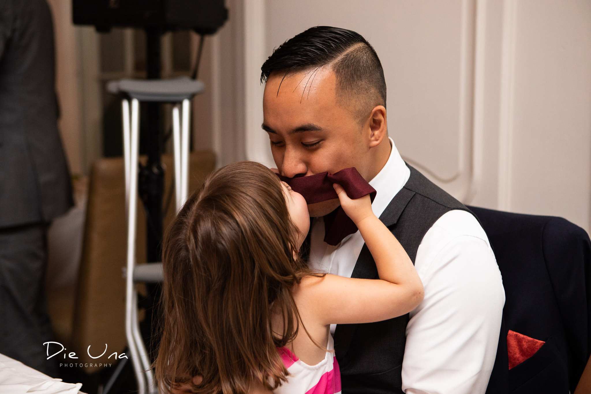 groom and neice being silly and share a kiss through groom's tie.jpg