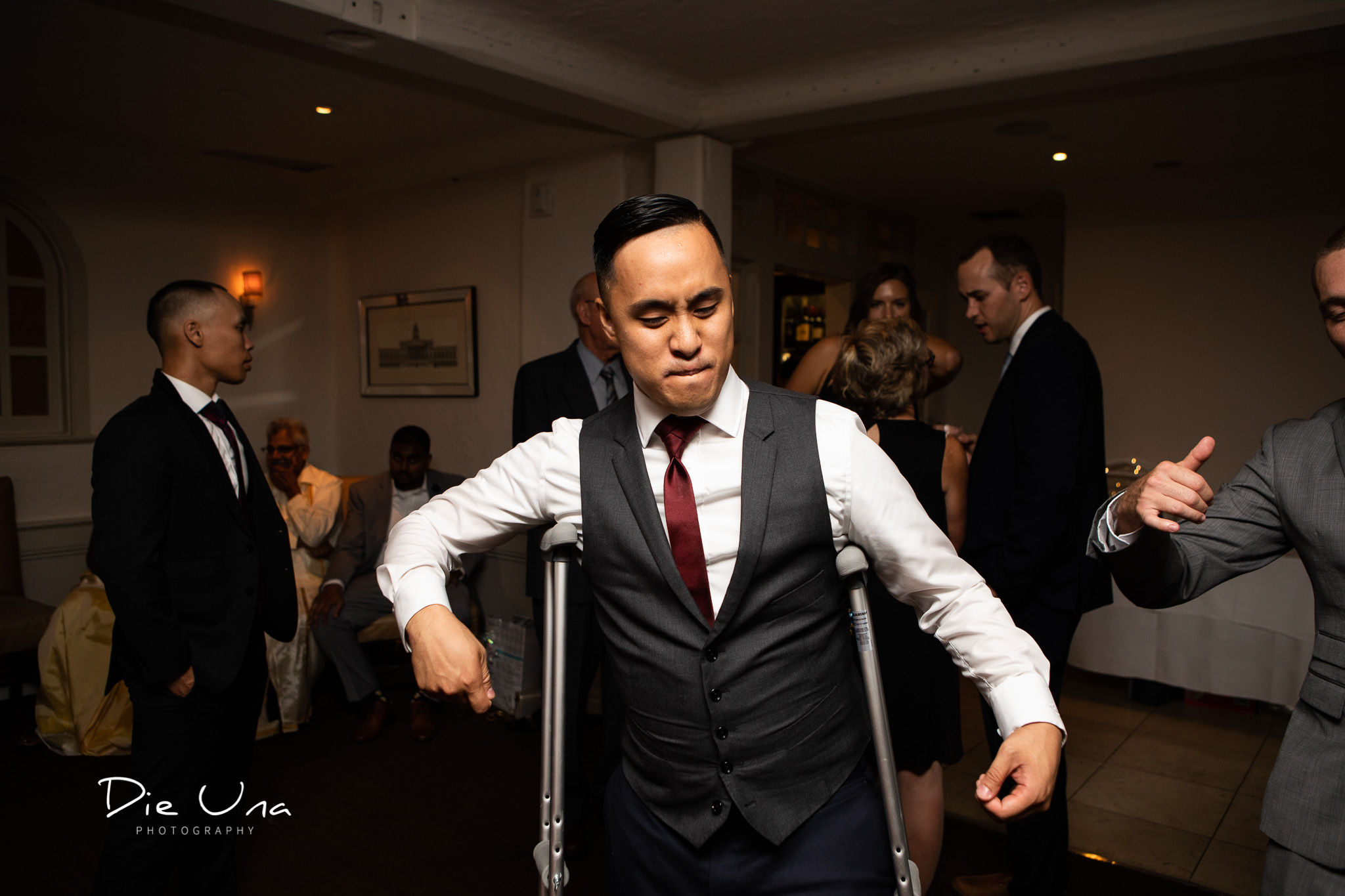 groom dancing during reception with crutches during wedding reception.jpg