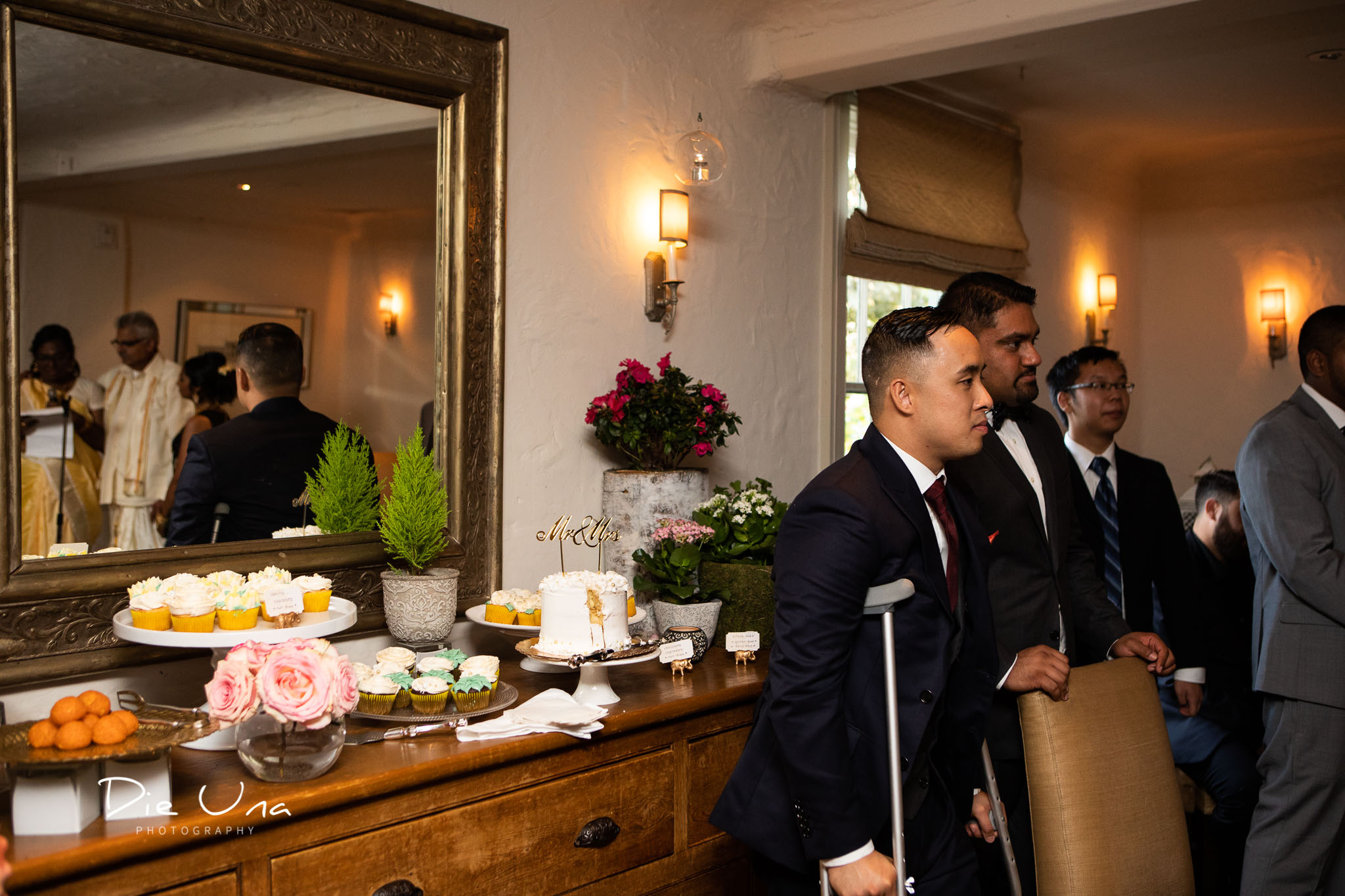 groom watching parents of the bride give a speech while they are reflected in a mirror.jpg