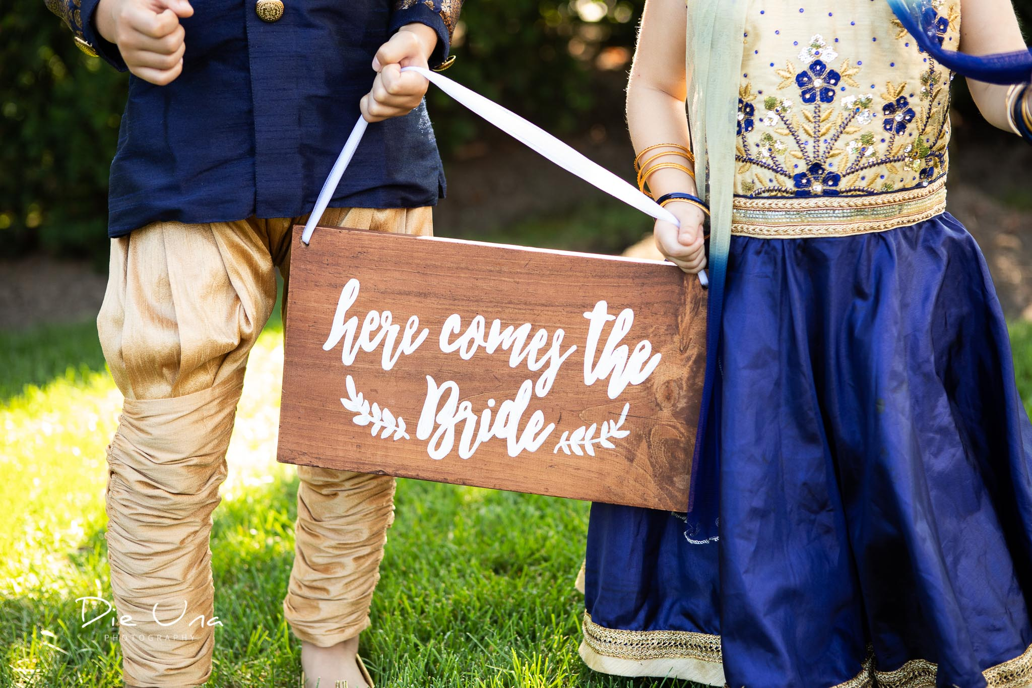 here comes the bride sign being held by flower girl and ringbearer in Hindu wedding.jpg