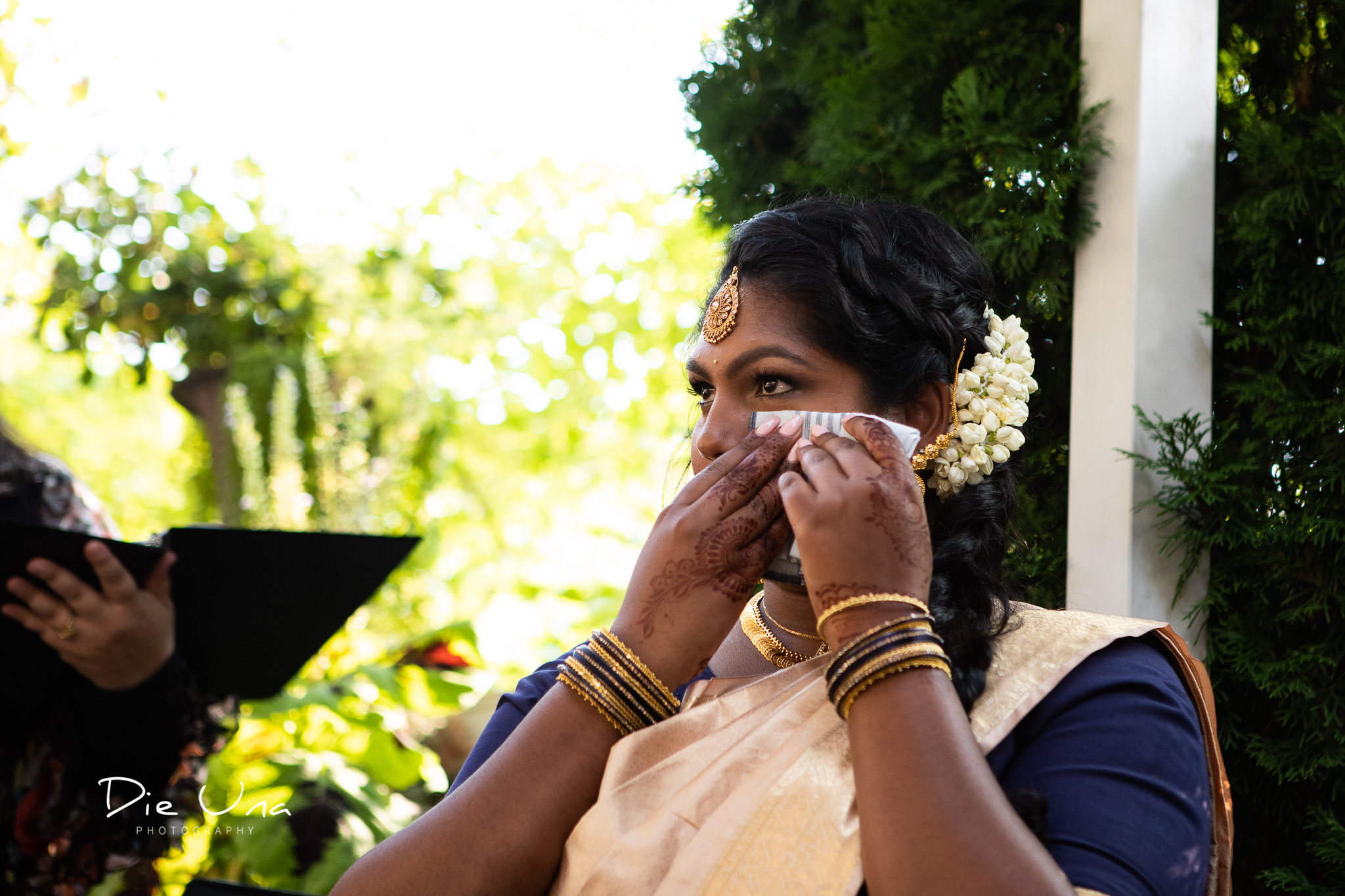 maid of honor wiping a tear from her eye during wedding ceremony.jpg
