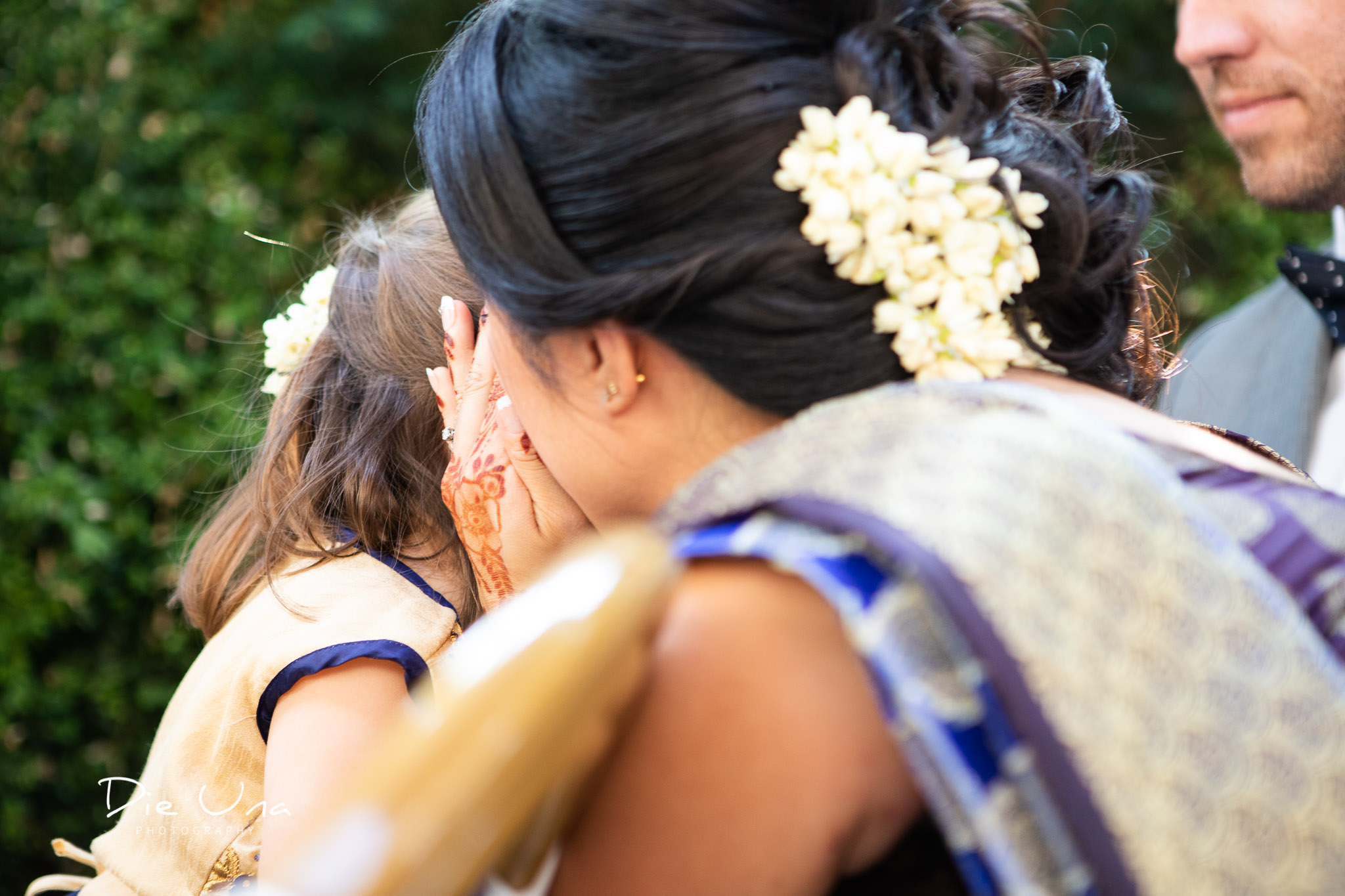 mom whispering to young duaghter during wedding ceremony.jpg
