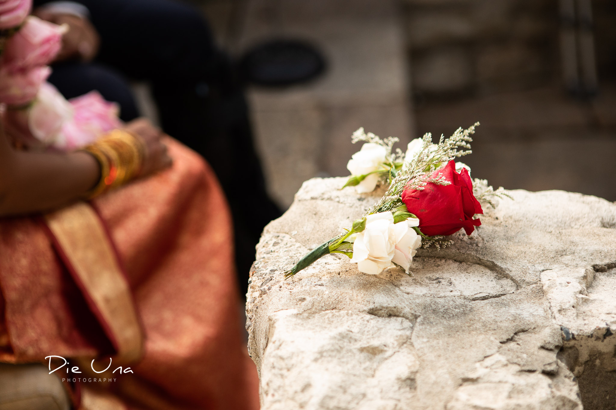 small hand held wedding bouquet resting on rock ledge during wedding ceremony.jpg
