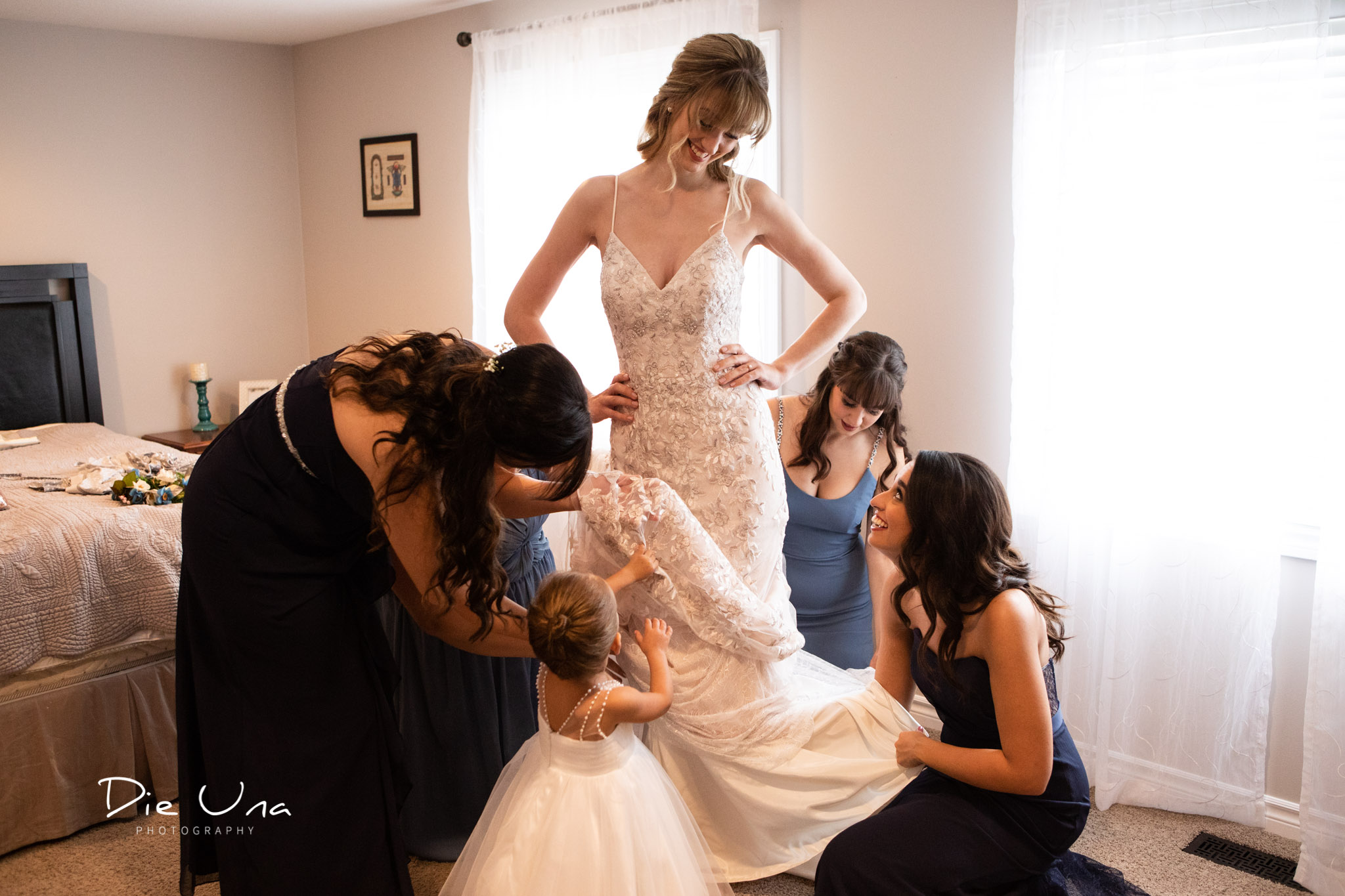 all the bridesmaids and flower girl helping the bride get her wedding dress on.jpg