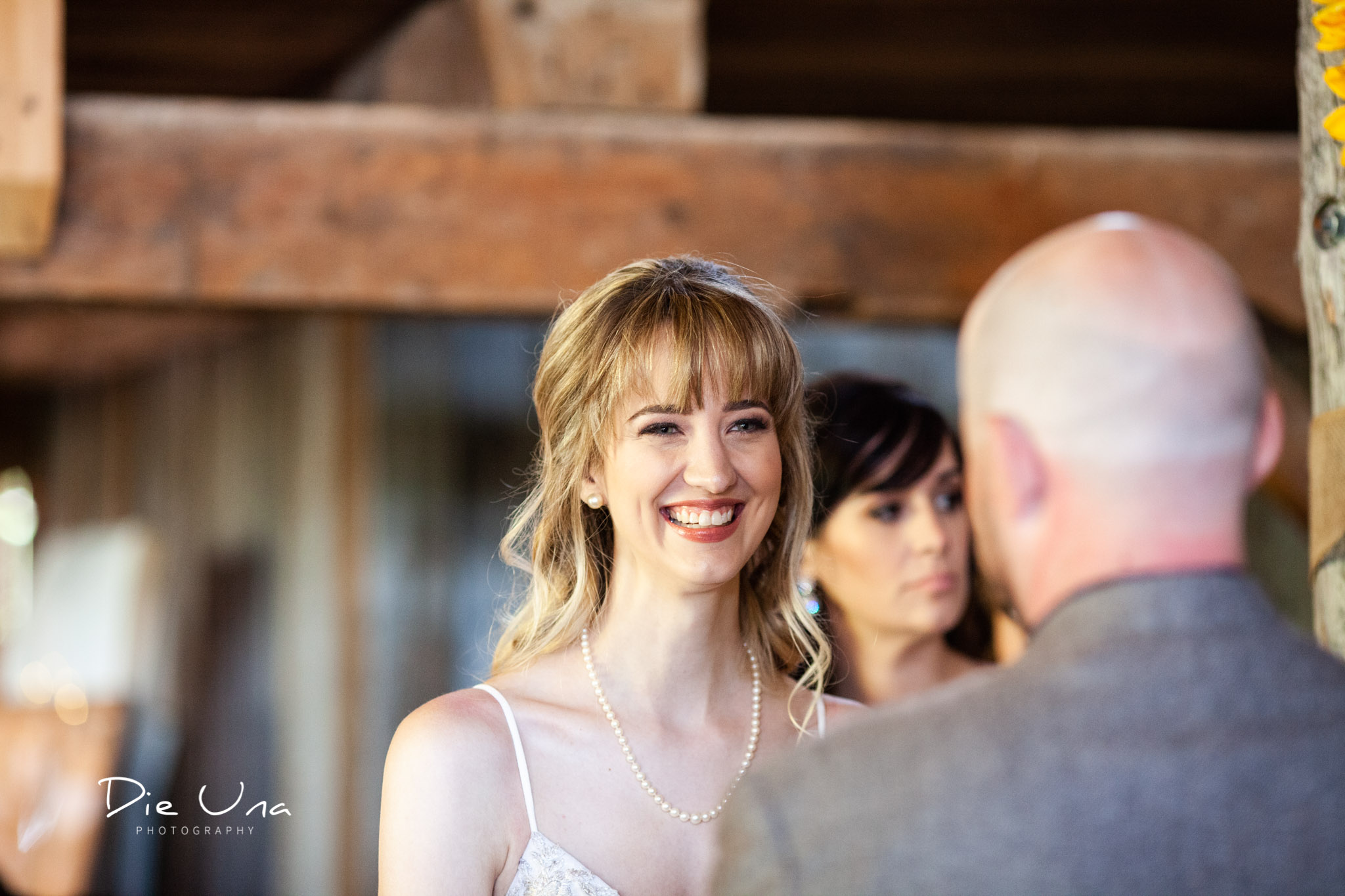 bride smiling at groom during wedding ceremony in a barn in southern ontario kitchener wedding photographer.jpg
