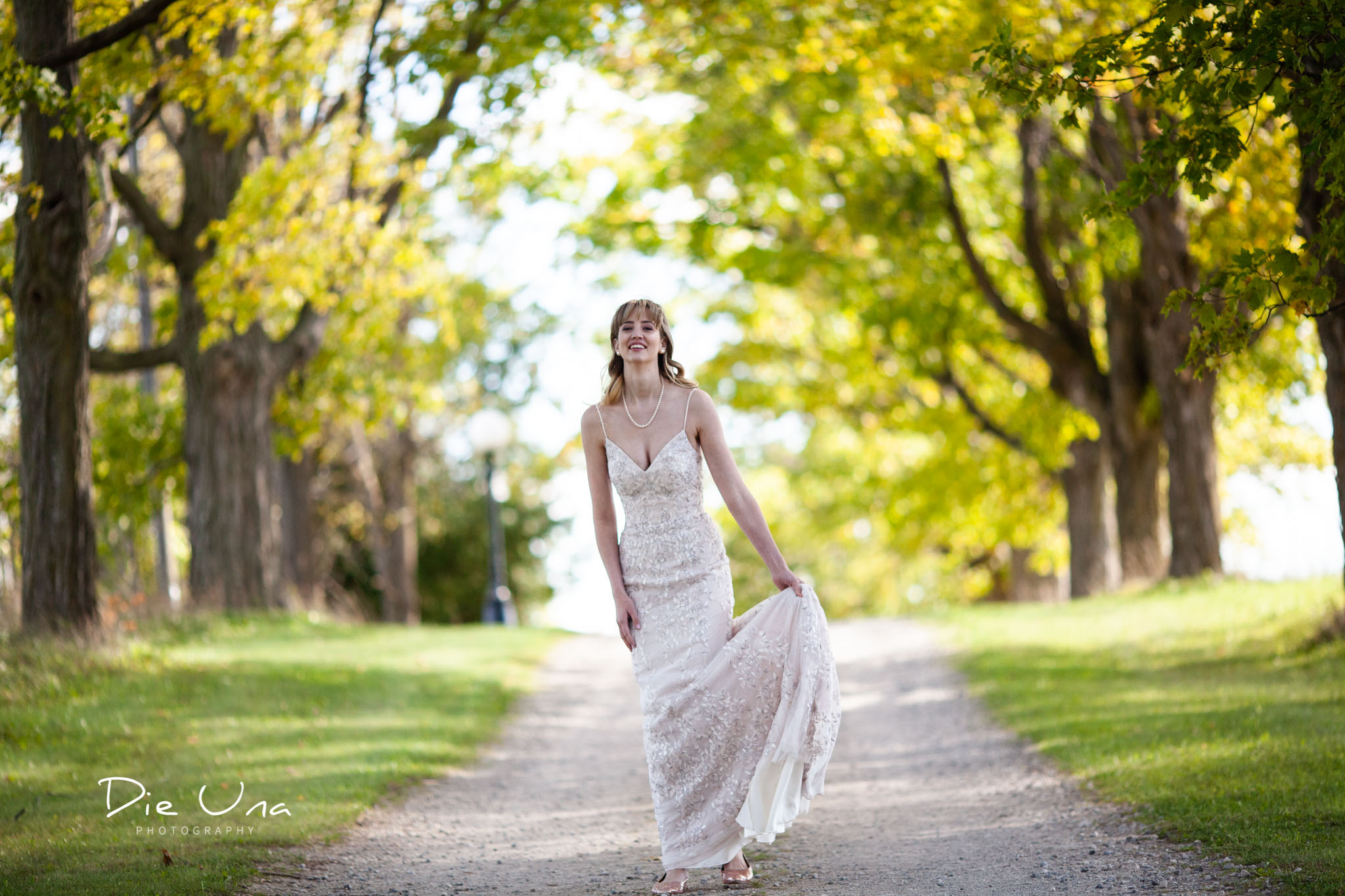 bride twirling wedding dress on tree lined driveway for wedding portraits.jpg