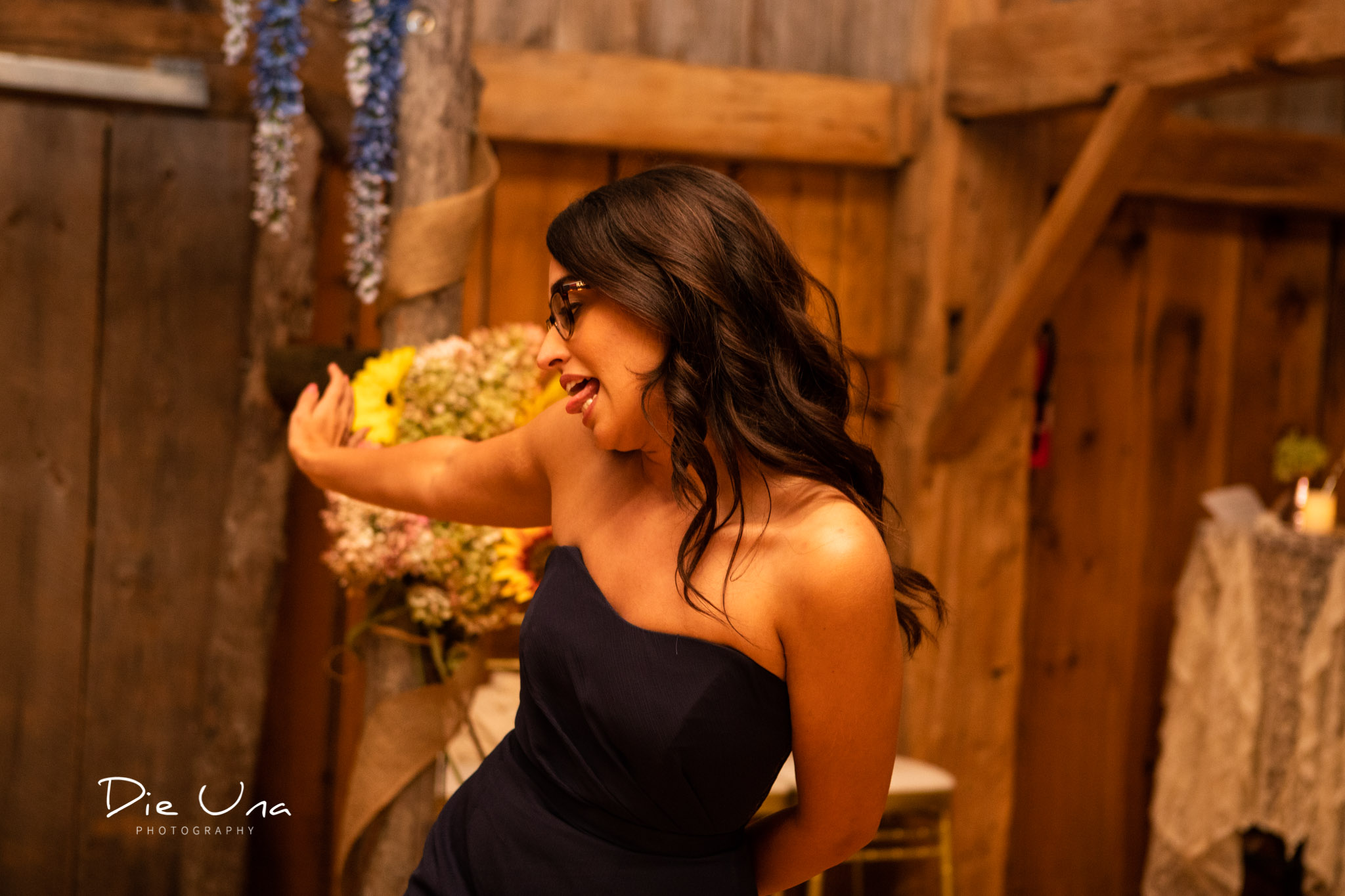 bridesmaid making a silly face during dance at wedding reception in a barn.jpg