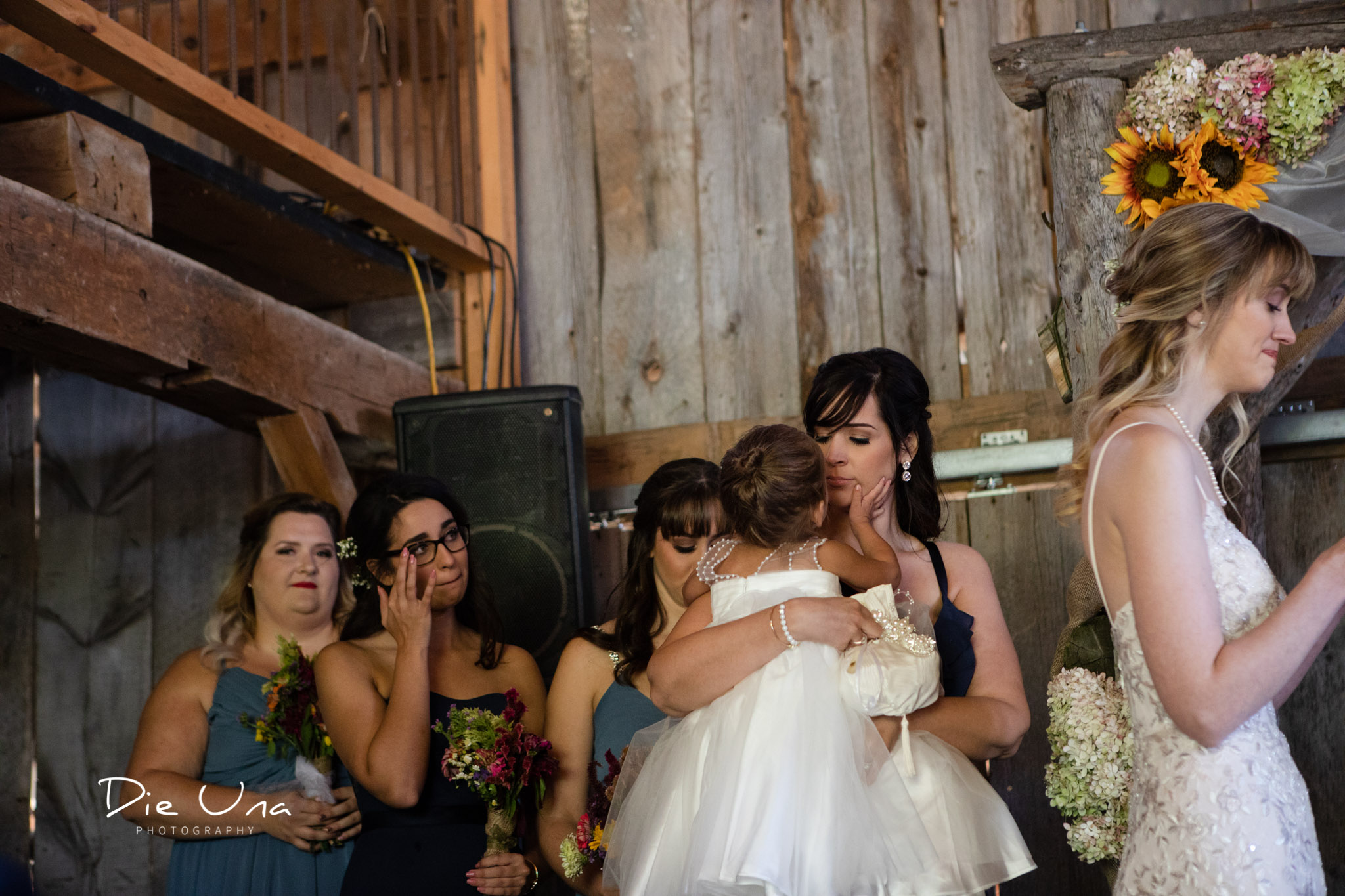 bridesmaids and flower girl crying during wedding ceremony in a barn in southern ontario.jpg