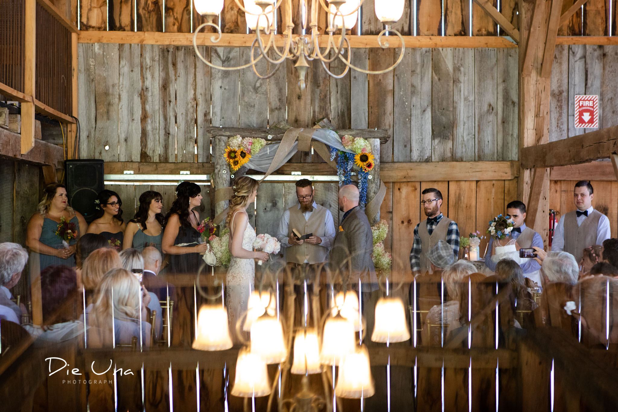 entire wedding party standing at the front of barn for wedding ceremony.jpg