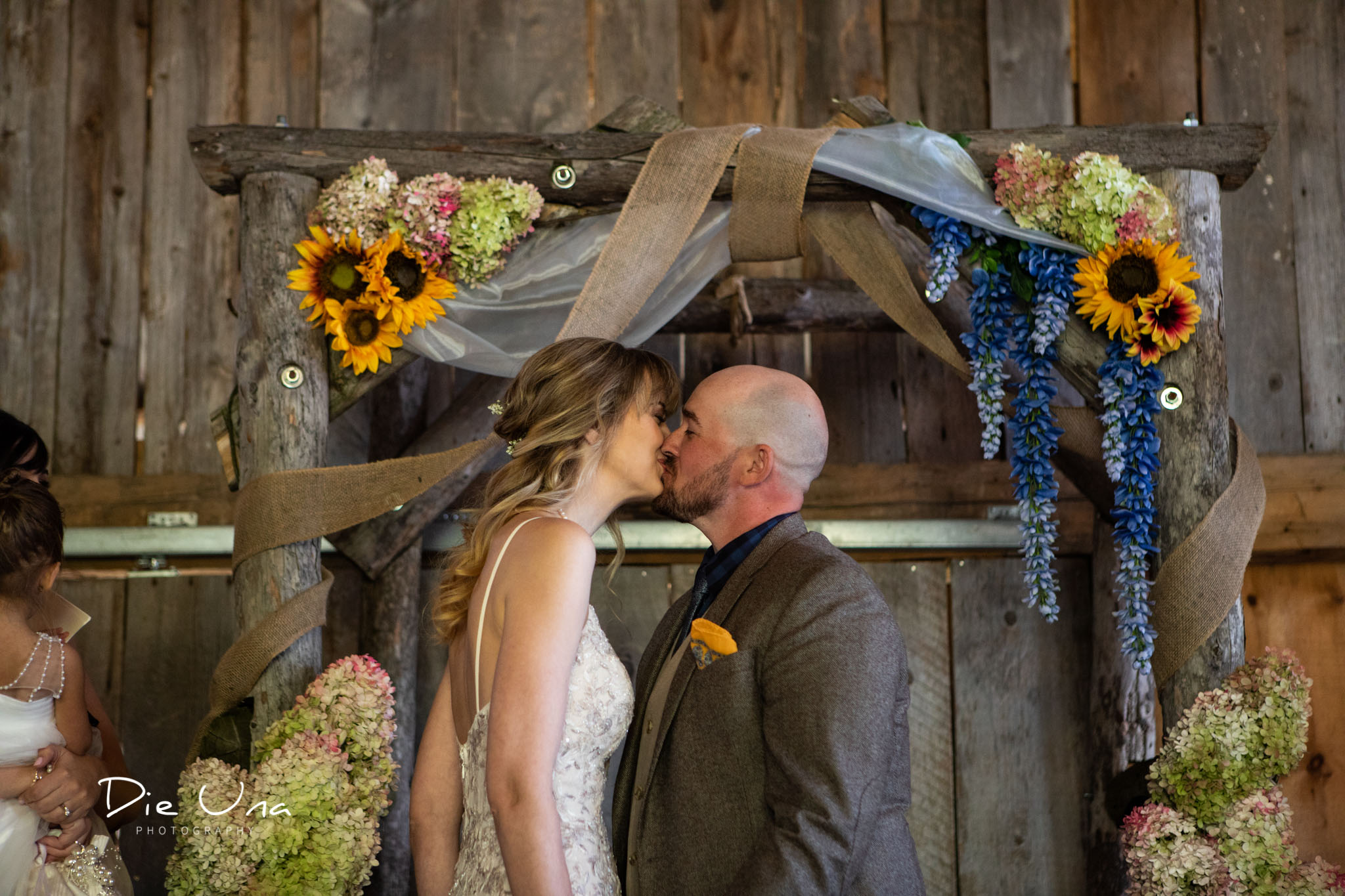 first kiss during barn wedding ceremony in southern ontario.jpg