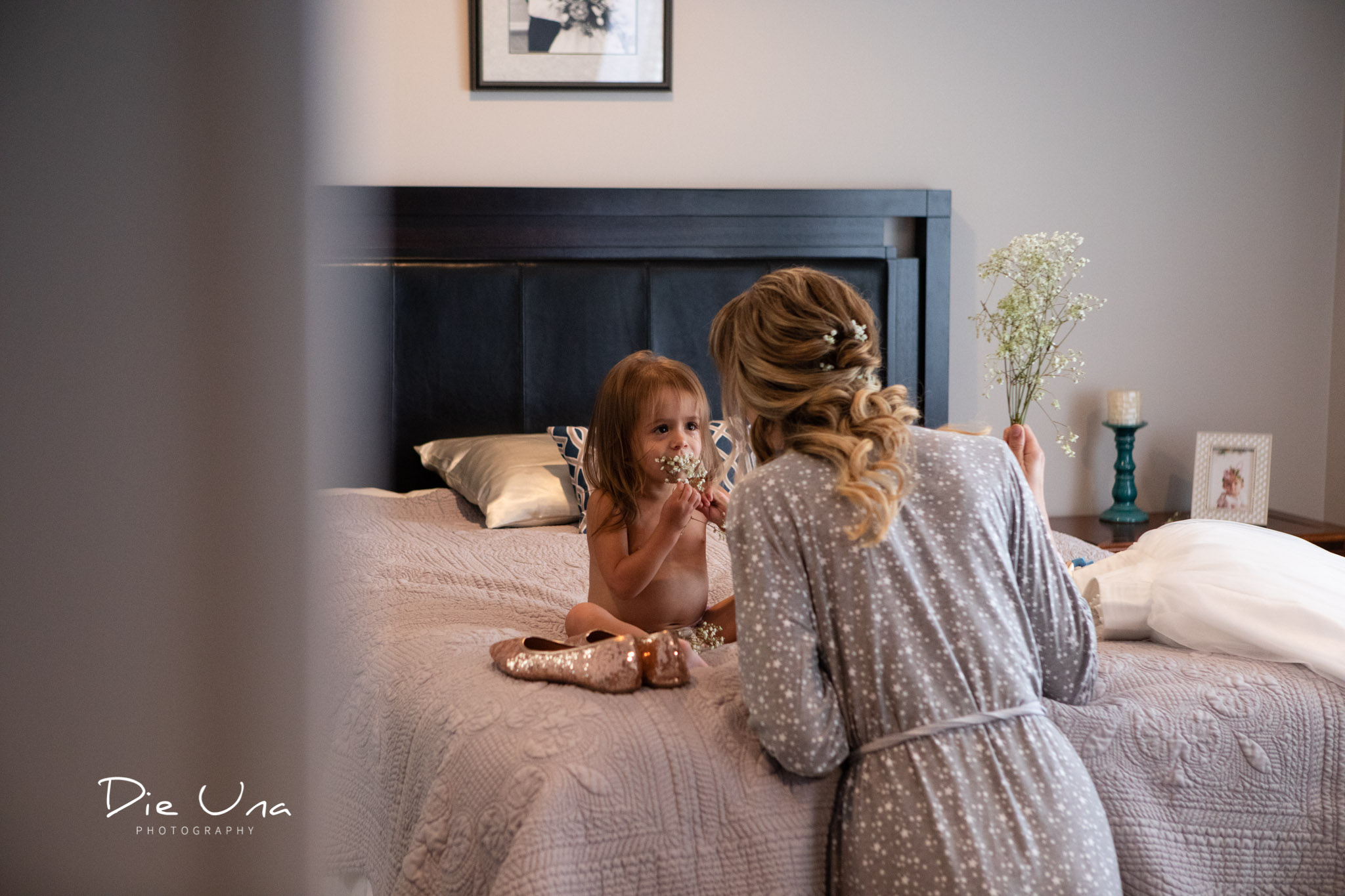 flower girl and bride having a touching moment while getting dressed for wedding.jpg