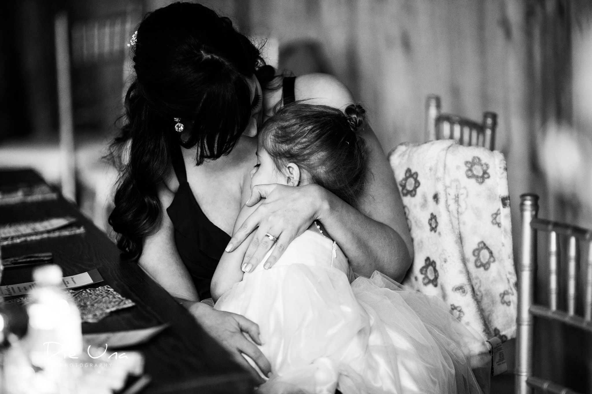 flower girl being hugged by her mom during wedding reception black and white wedding photography.jpg