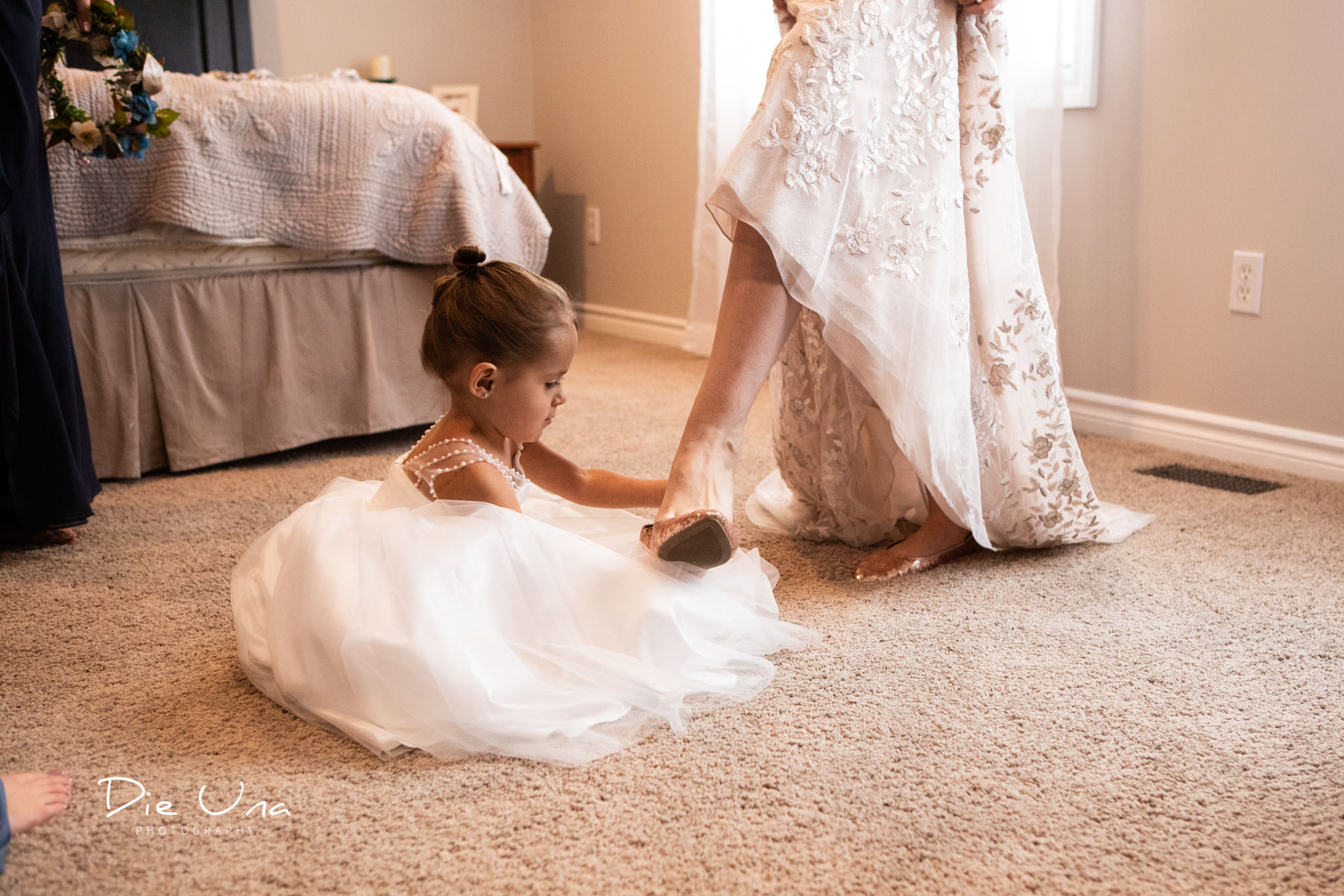 flower girl helping bride put on her wedding shoes.jpg