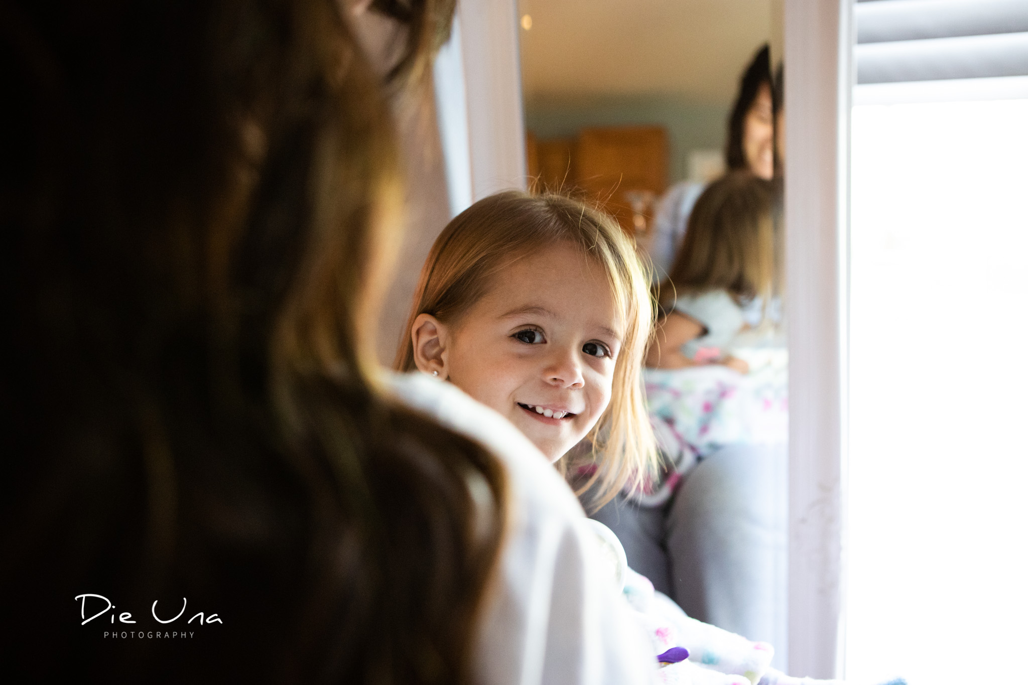 flower girl peaking over moms shoulder while getting ready for wedding.jpg